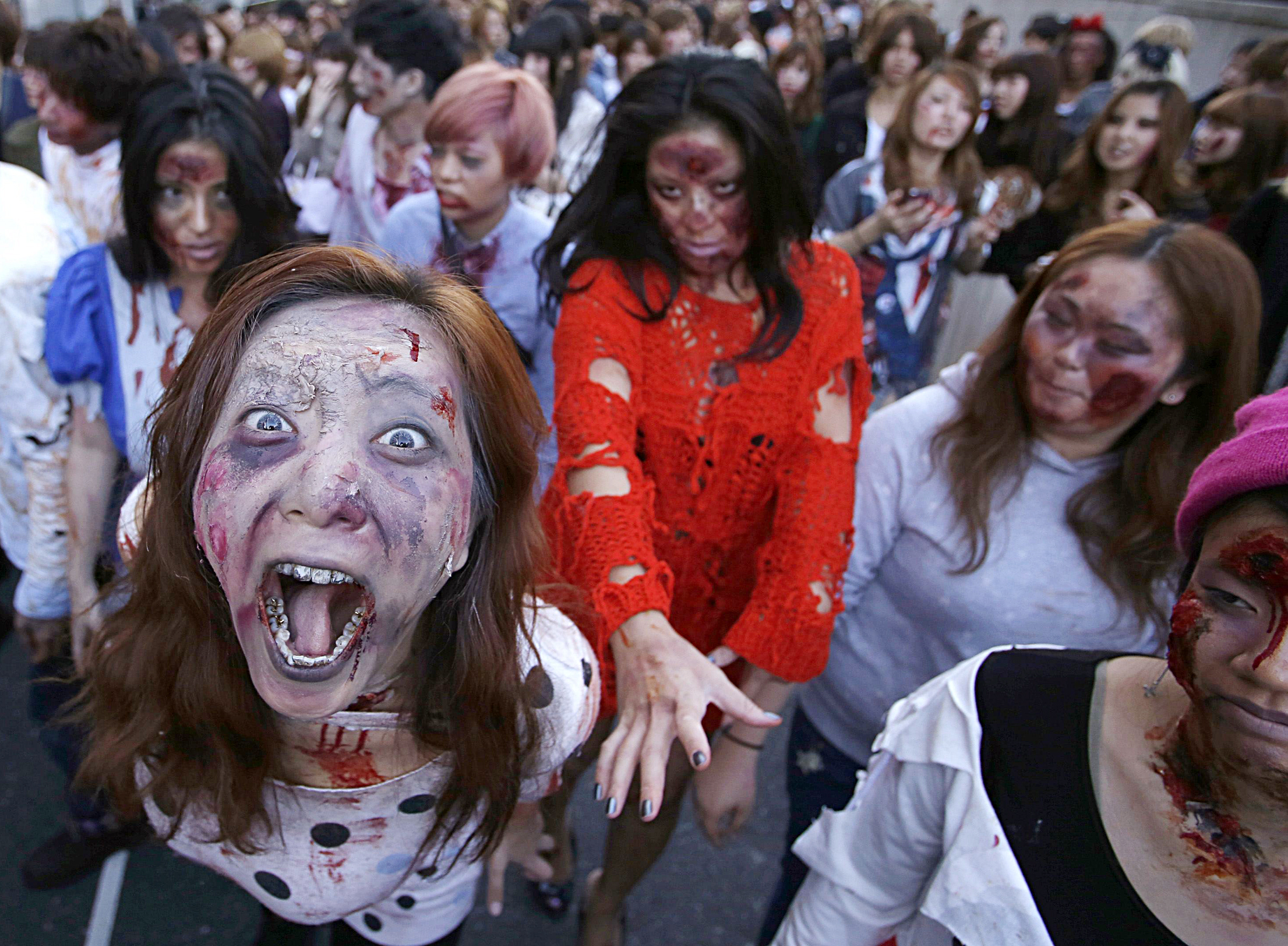 "Participants wearing costumes and make-up as zombies march during a Halloween event to promote the U.S. TV series ""The Walking Dead"" at Tokyo Tower...Participants wearing costumes and make-up as zombies march during a Halloween event to promote the U.S. TV series ""The Walking Dead"" at Tokyo Tower October 31, 2013. More than a thousand people dressed as zombies participated in the event to simulate taking over the tower, according to organisers.   REUTERS/Issei Kato"