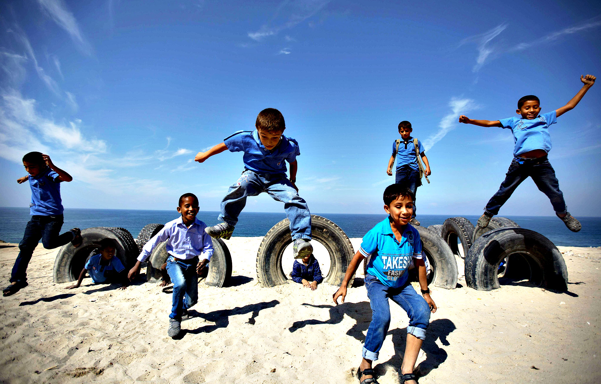 Palestinian school children play with tyres on ??Gaza beach on October 24, 2013 in Deir al-Balah.