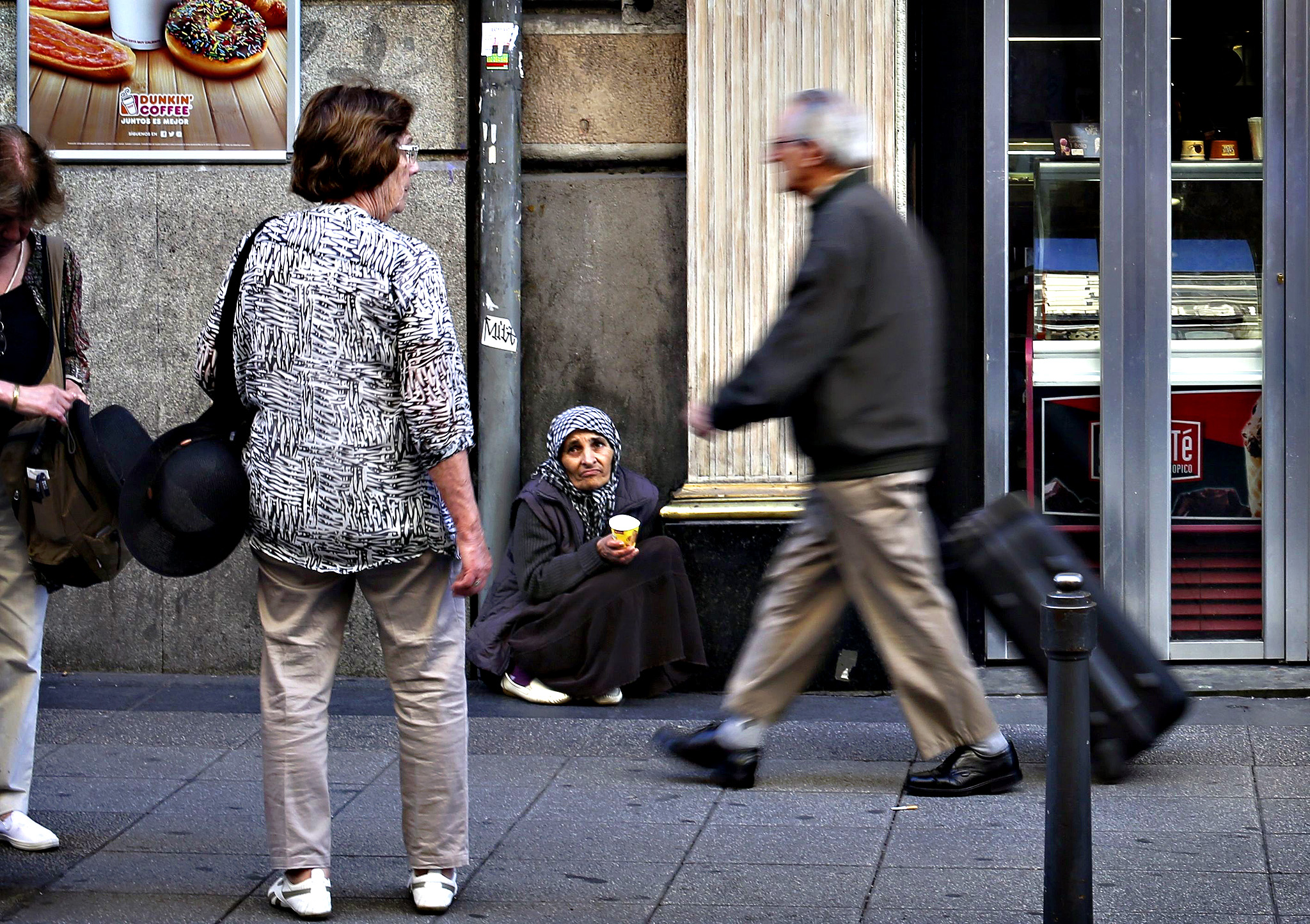 A beggar holds a plastic cup as people walk past in central Madrid, October 10, 2013. Beggars, dog-lovers and fortune-tellers who venture onto Madrid's busy streets may soon find themselves out of pocket as authorities in the city and elsewhere seek creative solutions to their financial problems.The Madrid council laid out plans this week to levy fines of 750 euros ($1,000) for public activities including soliciting for money outside shopping centres, feeding or washing dogs, reading tarot cards and performing acrobatics with a bike. Saddled with huge debts since a property bubble burst in 2008, Spain's autonomous regions and town halls have seen core revenues fall as unemployment holds stubbornly above 25 percent and corporate investments dry up. Many owe millions to service suppliers and staff.