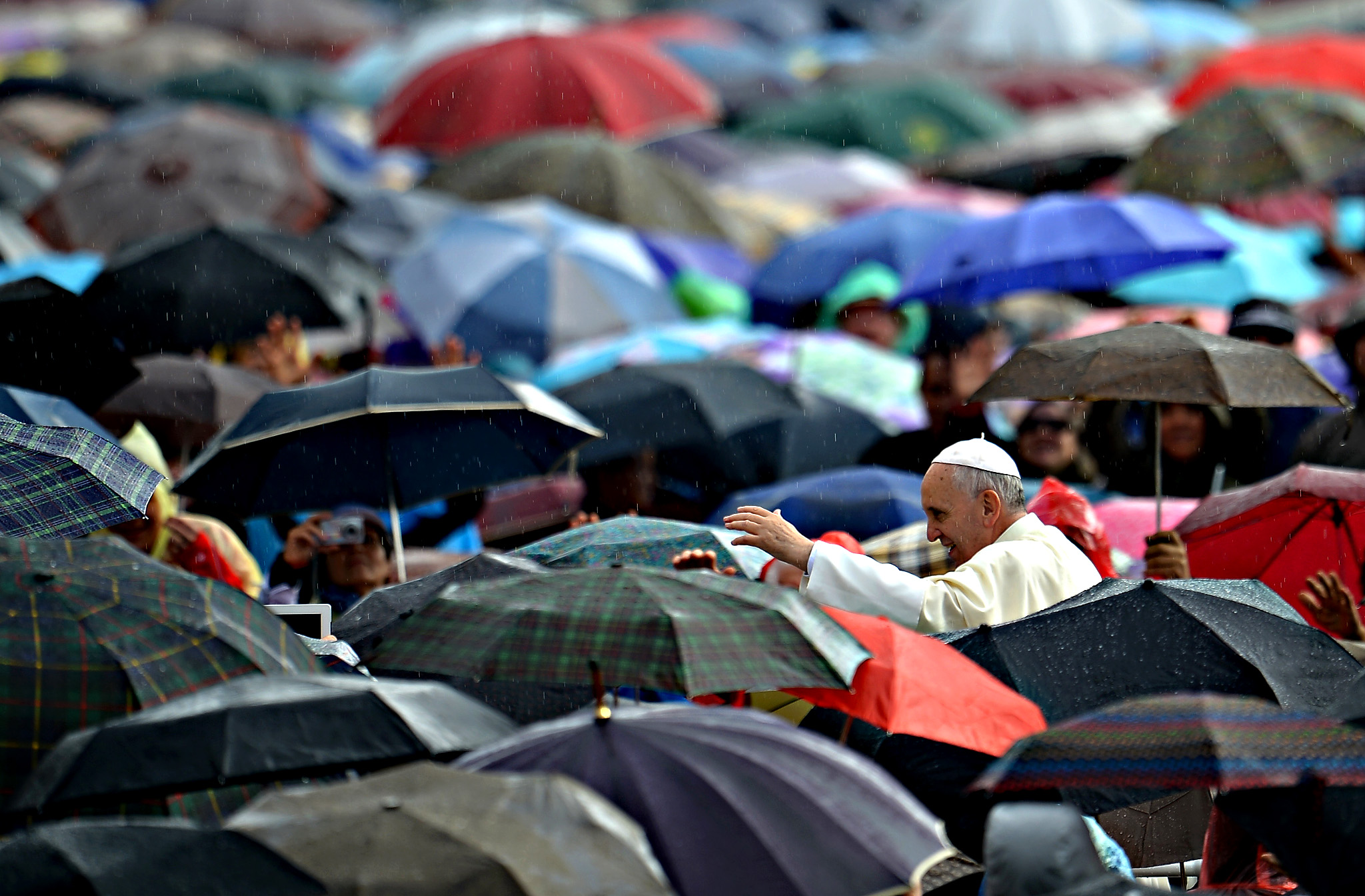 Pope Francis waves to crowds in the rain