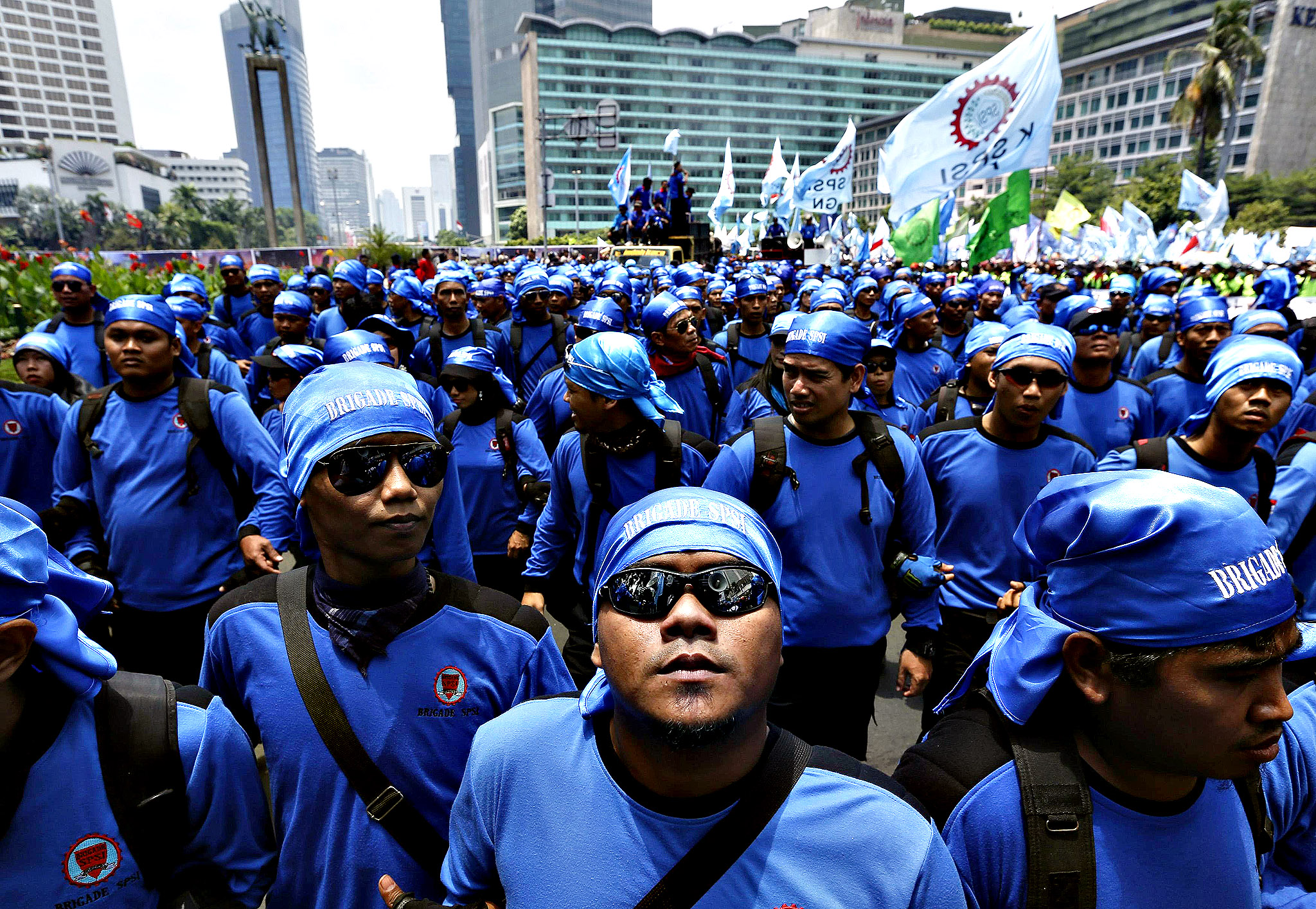 Union workers from Serikat Pekerja Seluruh Indonesia (SPSI) walk during a protest at the business district in Jakarta, October 17, 2013. Almost one thousand workers participated in the protest, demanding wage raises and objecting to outsourcing, according to local media on Thursday.