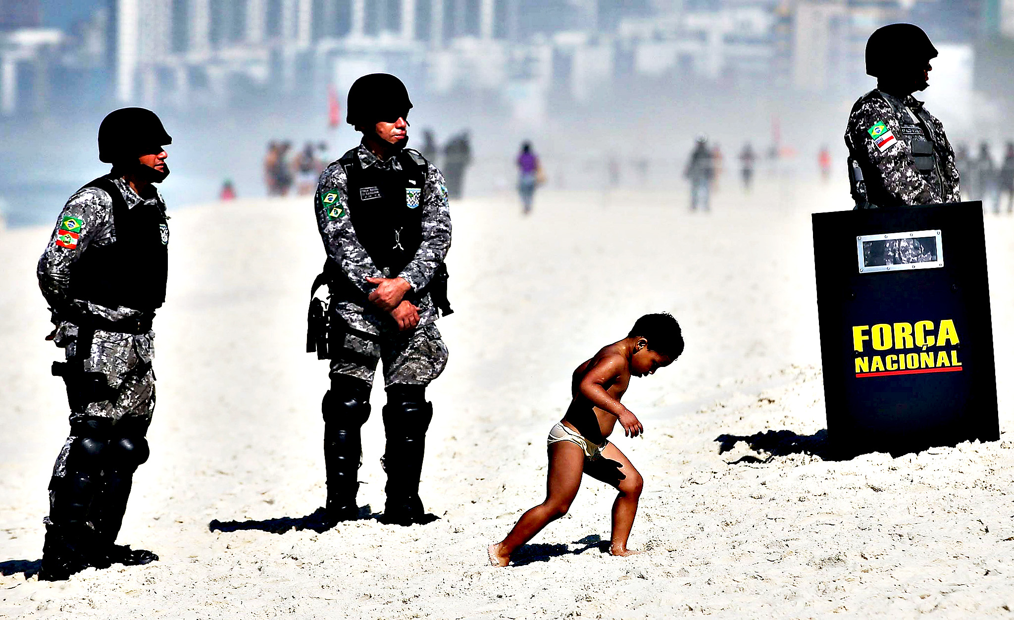 A boy walks past military police standing guard outside the seafront Windsor Barra hotel before the start of an auction of one of the world's biggest offshore oil finds on Monday in Rio de Janeiro, Brazil. Brazil is auctioning its Libra offshore oilfield which holds between 8-12 billion barrels of oil and protesters are demonstrating outside the hotel against the participation of foreign oil companies.