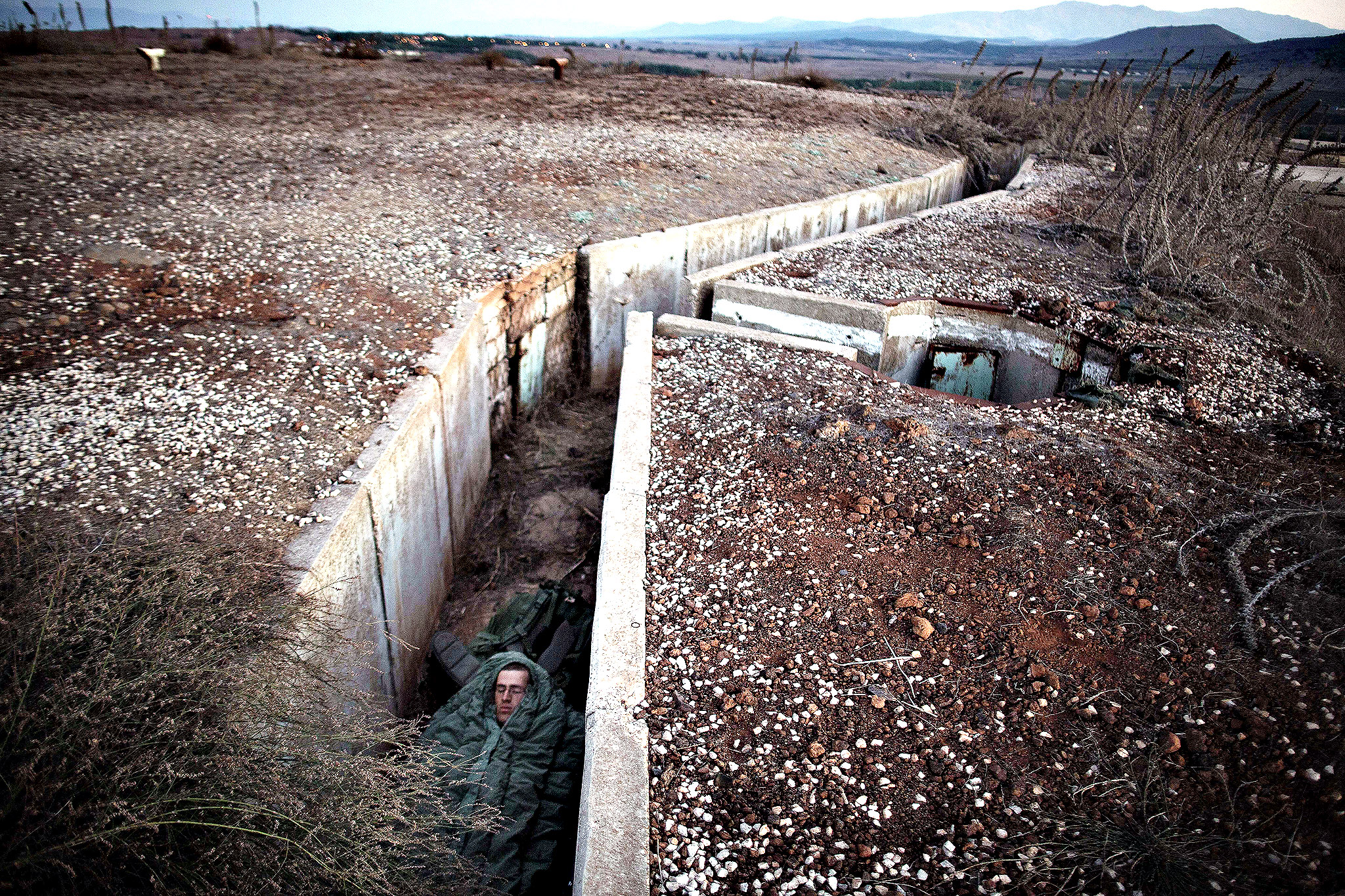 An Israeli soldier sleeps in a bunker in a training area in the Israeli-annexed Golan Heights during a brigade Armoured Corps Exercise on October 16, 2013. The Golan, seized by Israel from its Arab neighbour in the 1967 Six-Day War, has been mostly quiet since the 1973 Yom Kippur War. Tension, however, has risen since the 2011 start of the conflict in Syria between rebels and regime forces.