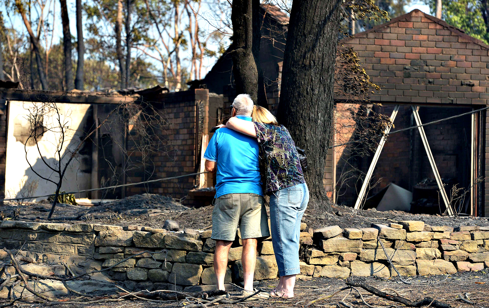 "A couple look at a house burnt out by bushfires in Winmalee in Sydney's Blue Mountains. Residents faced scenes of devastation on Friday after bushfires ravaged communities and destroyed ""hundreds"" of homes in southeastern Australia with dozens of blazes still burning out of control."