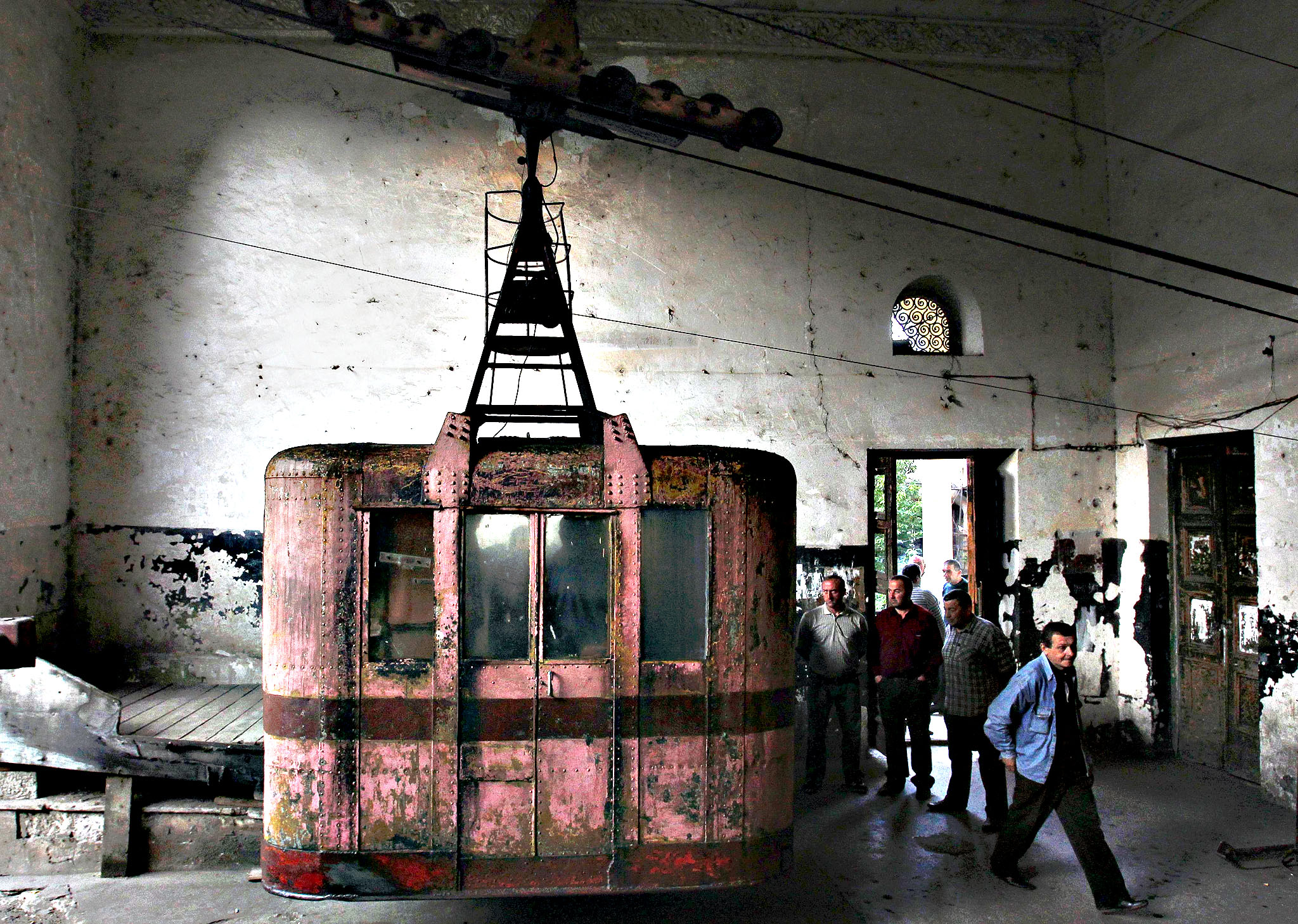 Commuters get out of a 60-year-old cable car in the town of Chiatura, some 220 km (136 miles) northwest of Tbilisi, September 12, 2013. Dating to the Soviet era, Chiatura's public cable cars were built to facilitate the manganese mining industry, which formed the bedrock of the town's economy. Sixty years later, 15 of Chiatura's 21 cable car routes are still running, covering a total length of over 6000 meters, and they are still the quickest and most convenient way of getting around, despite their advanced years.