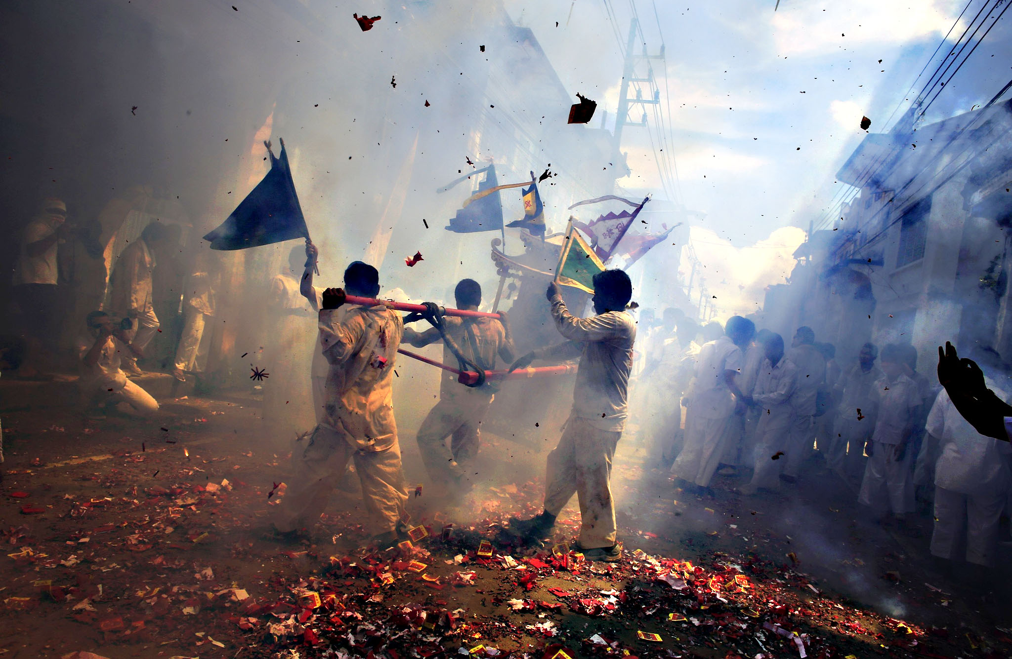 Devotees of Chao Pho Kuan U shrine carry a statue through exploding firecrackers during a street procession during the annual vegetarian festival in Phang Nga October 10, 2013. The festival, featuring face-piercing, spirit mediums and strict vegetarianism celebrates the local Chinese community's belief that abstinence from meat and various stimulants during the ninth lunar month of the Chinese calendar will help them obtain good health and peace of mind.