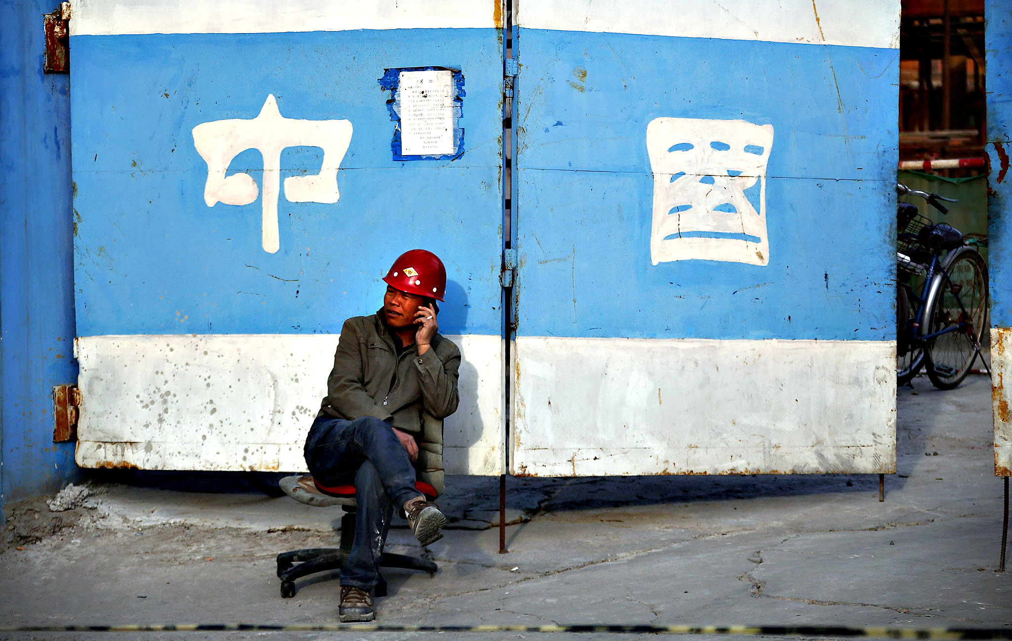 "A man talks on his mobile phone outside a construction site in central Beijing. China's government wants to prevent a bubble from forming and head off unrest if people cannot afford to buy homes. However, it cannot tighten too much as a strong property market has helped offset an economic slowdown. The Chinese characters behind on the gate read, ""China""."