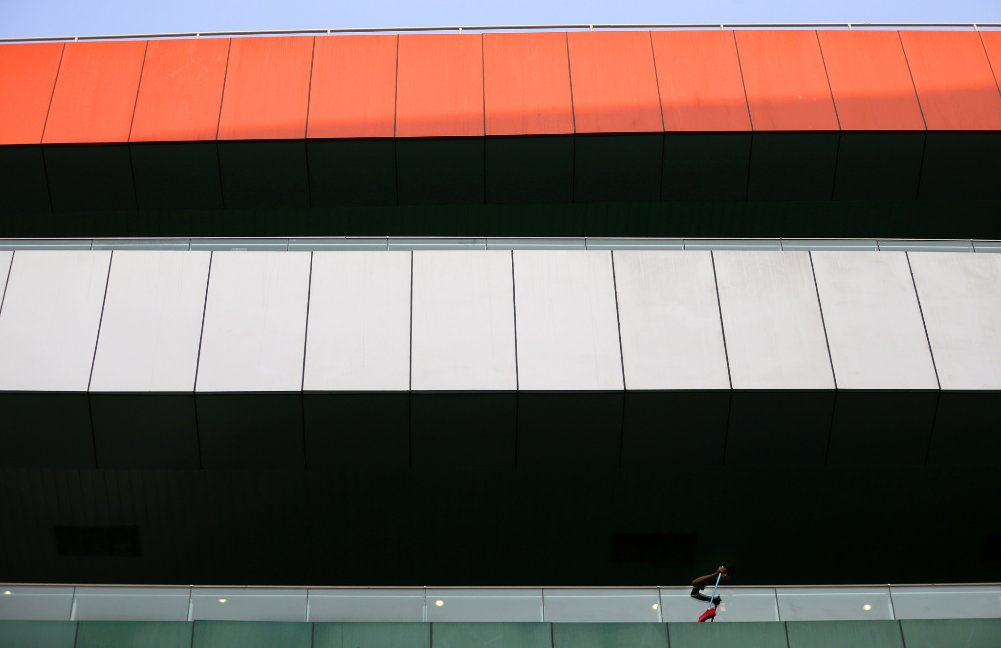 A cleaner sweeps a balcony of a grandstand ahead of the Indian Formula One Grand Prix at the Buddh International Circuit in Noida, India, Thursday, Oct. 24, 2013.