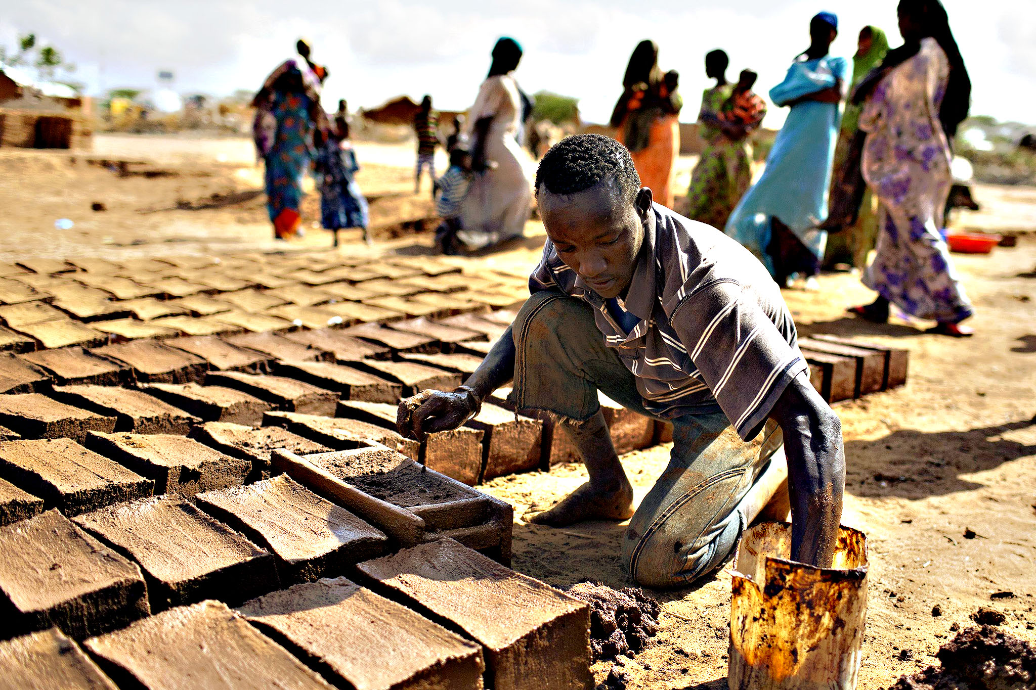 A man makes construction bricks from mud at one of several refugee settlements in Dadaab, Garissa County, northeastern Kenya.
