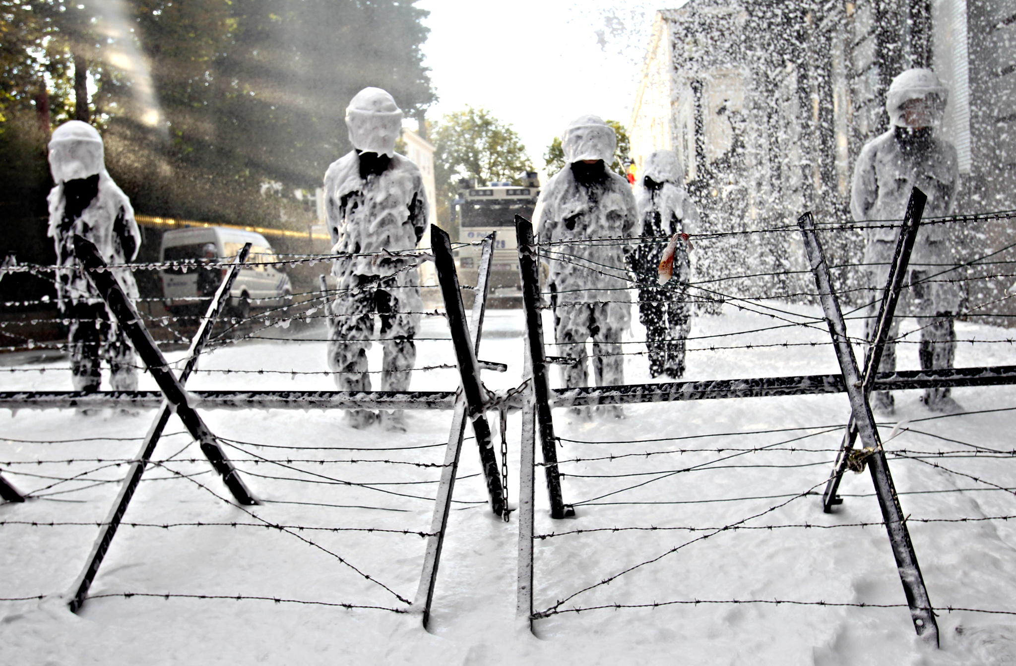 Policemen stand guard while firefighters are spraying foam from behind the barricades