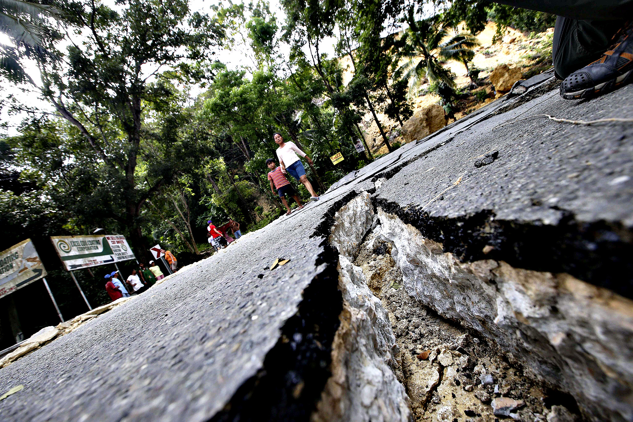 Filipinos walk along the road destroyed by a 7.2-magnitude earthquake  in Cortez  town, Bohol province, central Philippines, 16 October 2013. The death toll in a powerful earthquake in the Philippines has risen to 144, the national disaster risk management agency said 16 October.  At least 23 were reported missing and believed trapped in collapsed buildings in Bohol Province, 640 kilometres south of Manila, it added. Nearly 300 were injured in October 15  magnitude-7.2 tremor, the worst to hit the Philippines in two decades.