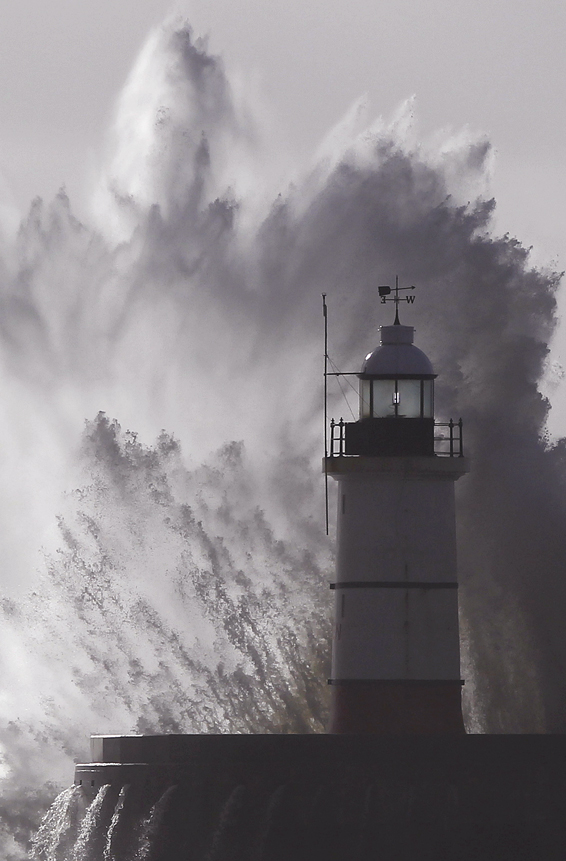 Waves crash against a lighthouse during storms that battered Britain and where a 14-year-old boy was swept away to sea at Newhaven in South East England...Waves crash against a lighthouse during storms that battered Britain and where a 14-year-old boy was swept away to sea at Newhaven in South East England October 28, 2013. Britain's strongest storm in a decade battered southern regions on Monday, forcing hundreds of flight cancellations, cutting power lines and disrupting the travel plans of millions of commuters. Police said rescuers were forced to call off a search for the boy late on Sunday due to the pounding waves, whipped up by the rising wind. REUTERS/Luke MacGregor