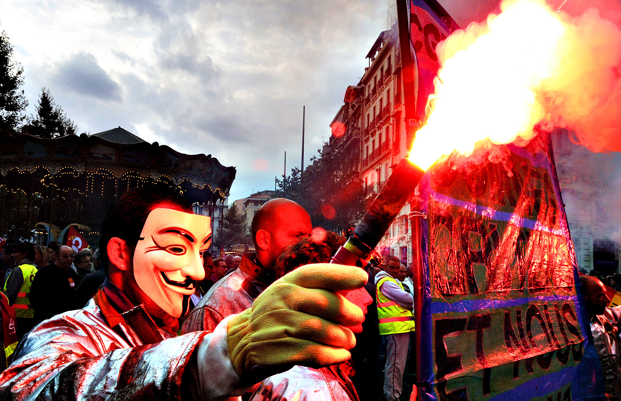 A man wearing a mask burns a flare on October 15, 2013 in Marseille, southern France, as he takes part in a protest called by French workers' unions (UNEF, UNL, CGT, FSU and FO), against the government's plans to reform France's retirement system.