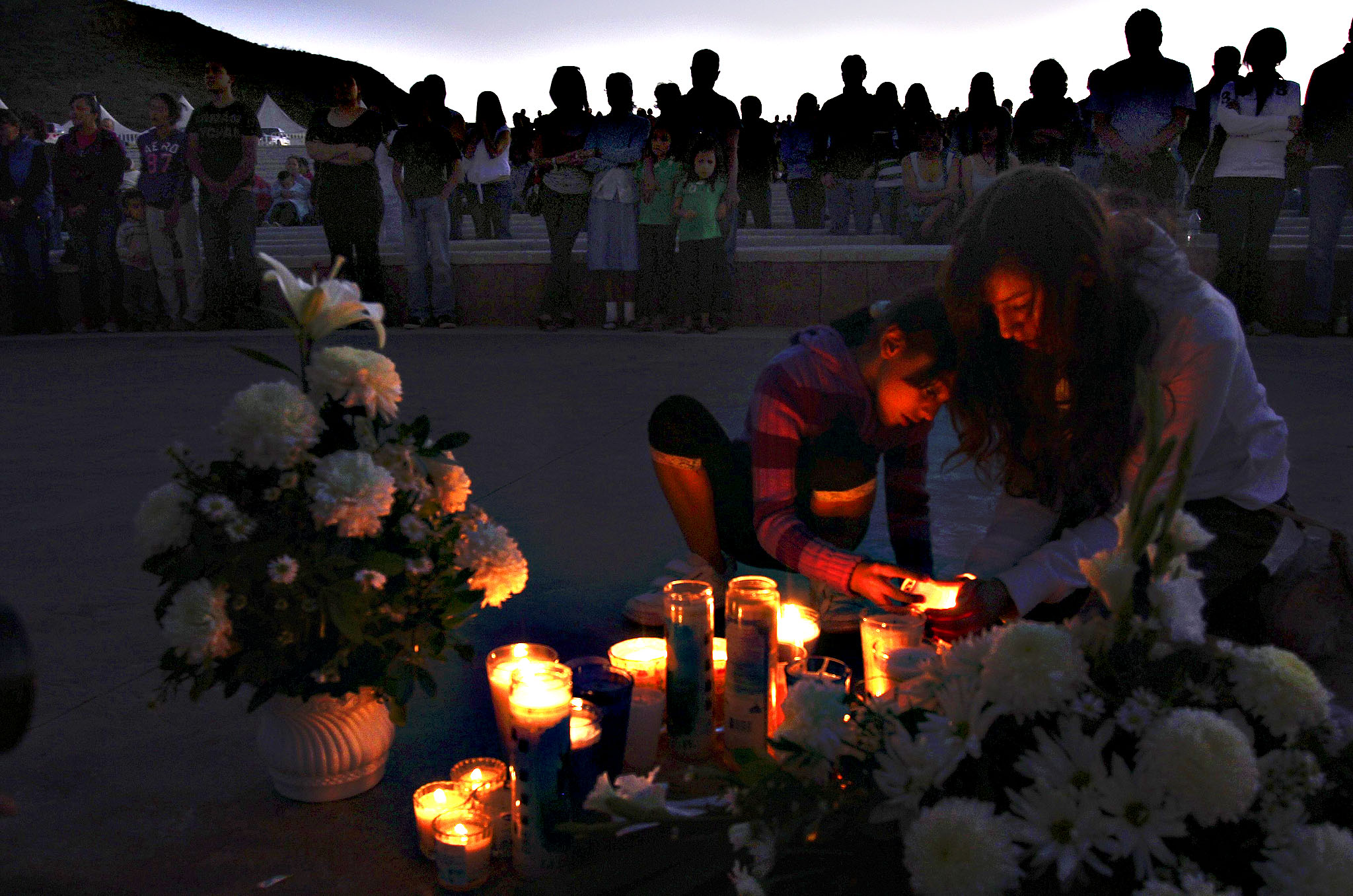 Girls light candles during a candlelight vigil for the victims of a monster truck that ploughed into a crowd of spectators during a show at El Rejon park in Chihuahua...Girls light candles during a candlelight vigil for the victims of a monster truck that ploughed into a crowd of spectators during a show at El Rejon park, on the outskirts of Chihuahua October 6, 2013. Eight people, including four children, were killed and 79 injured when a monster truck careened into a crowd at a show in northern Mexico, an official at the public prosecutor's office in the city of Chihuahua said on Sunday. The incident late on Saturday afternoon took place at the El Rejon dam on the outskirts of the city, about 230 miles (370 km) south of Mexico's border with the United States.