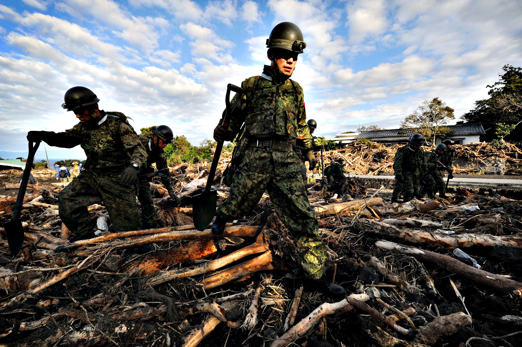 Ground Self-Defense Force rescue member search for survivors after a landslide caused by heavy rains brought on by typhoon Wipha buried houses at Oshima island, 120km south of Tokyo on October 17, 2013. At least 17 people died as a powerful typhoon lashed Japan's Pacific coast, with dozens still missing and the death toll likely to rise.