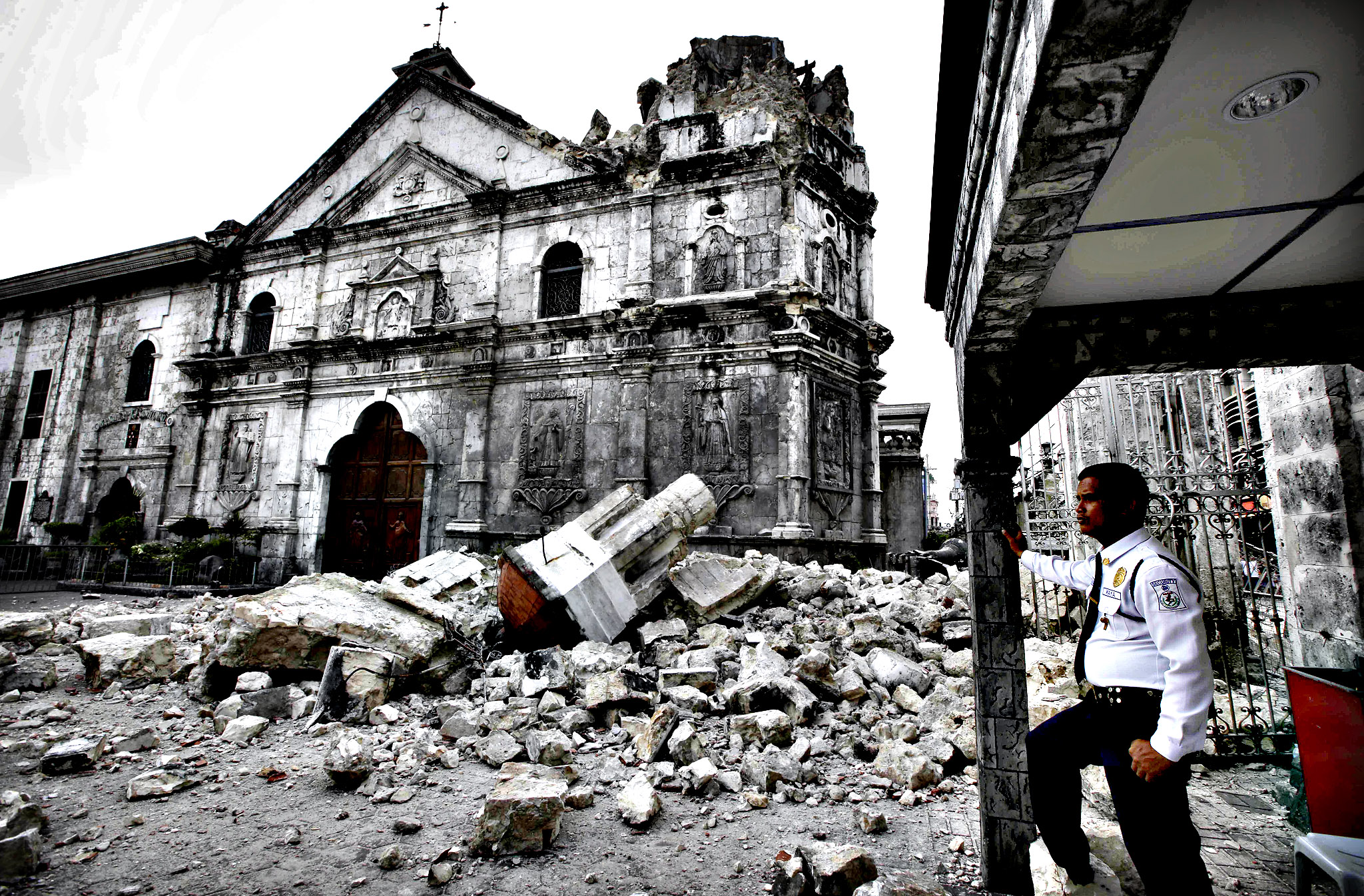 A private guard stands near the damaged Basilica of the Holy Child following a 7.2-magnitude earthquake that hit Cebu city in central Philippines and toppled the bell tower of the Philippines' oldest church Tuesday, Oct. 15, 2013. The tremor collapsed buildings, cracked roads and toppled the bell tower of the Philippines' oldest church Tuesday morning, causing multiple deaths across the central region and sending terrified residents into deadly stampedes.