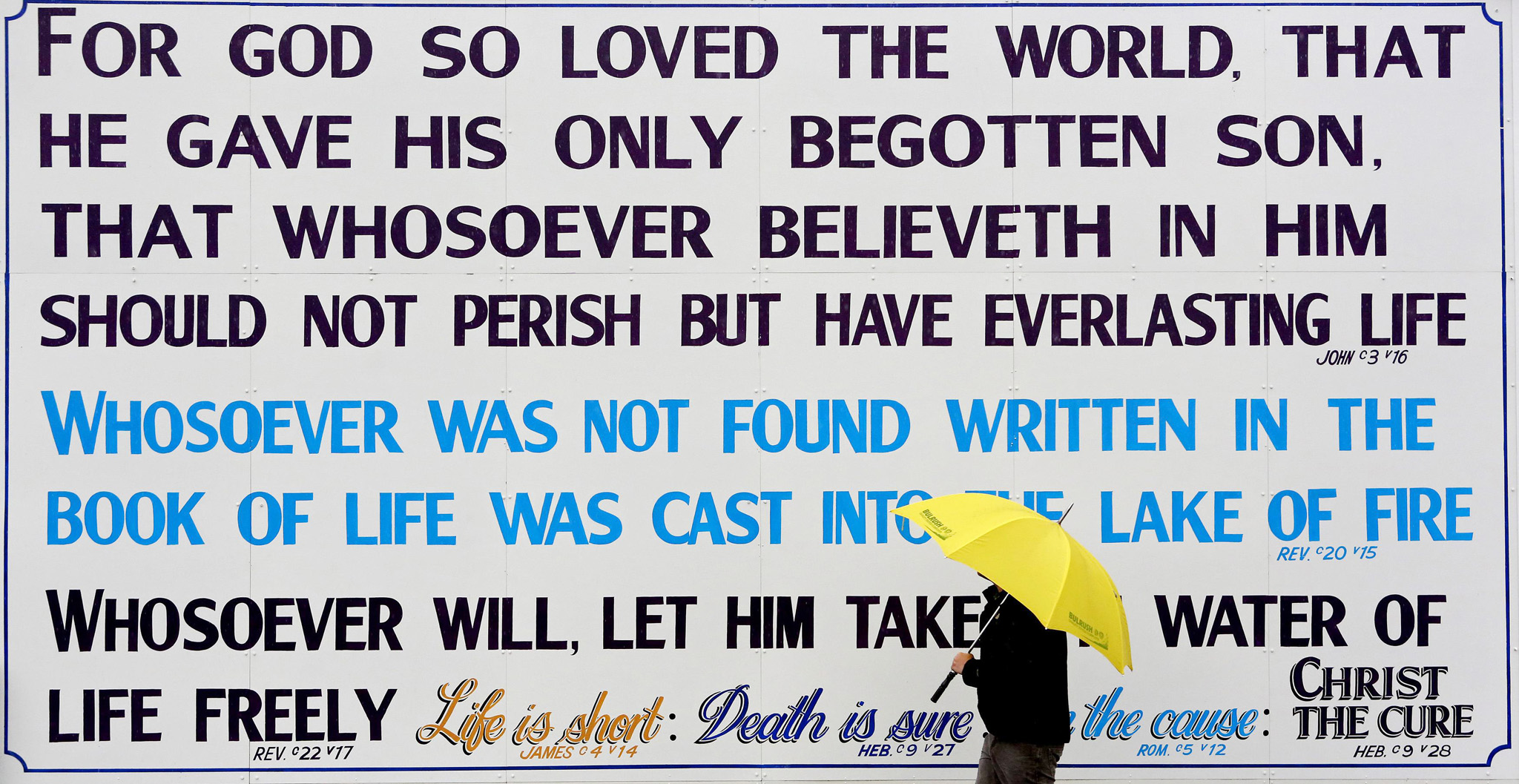 A man walks past religious scripture painted on a wall in the seaside village of Portrush near the Giants Causeway in Northern Ireland...A man walks past religious scripture painted on a wall in the seaside village of Portrush near the Giants Causeway in Northern Ireland October 16, 2013.   REUTERS/Cathal McNaughton