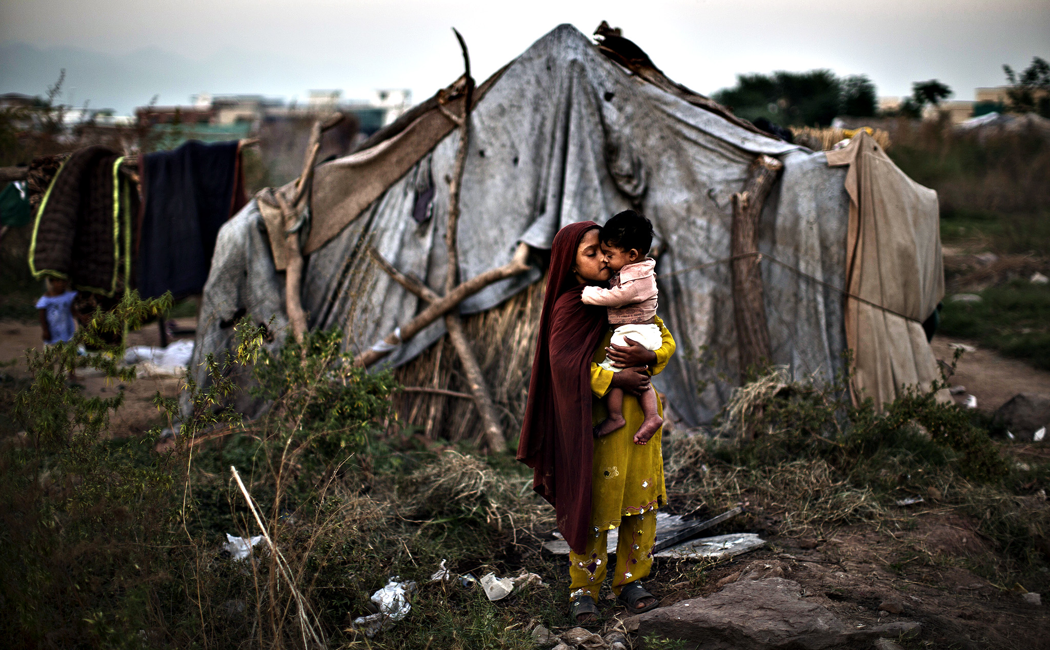 A Pakistani girl comforts her brother near her family's makeshift tent in a slum in Islamabad, Pakistan, Monday, Oct. 21, 2013. Slums, which are built on illegal lands, have neither running water or sewage disposal.