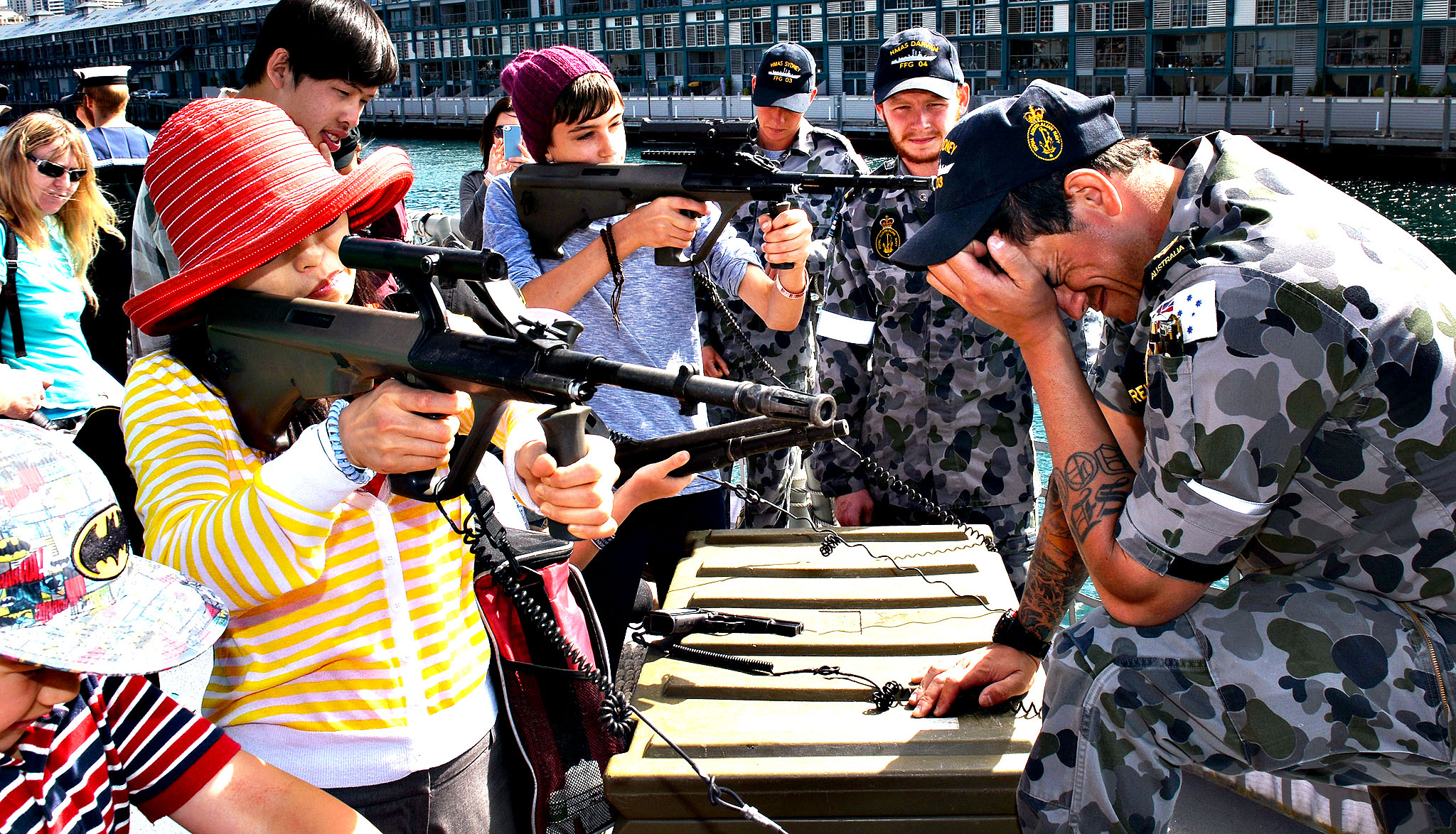 Visitors try out small weapons on the HMAS Darwin at Royal Australian Navy's Sydney base of Garden Island, during an open day after the Navy celebrated 100 years since their first ships entered Sydney Harbour, on October 7, 2013.  The open day followed the Royal Australian Navy International Fleet Review which also included visiting warships from Britain, Singapore, Japan, India, Thailand and the United States.