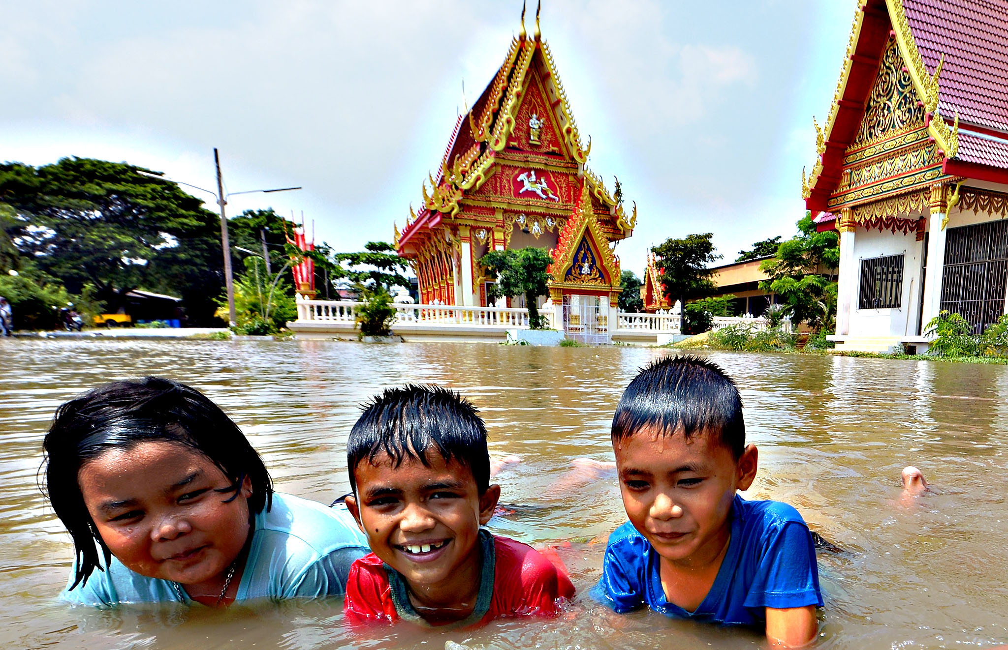 Thai children enjoy play in floodwaters at a buddhist temple in Pathum thani province, north of Bangkok on October 9, 2013. The Disaster Prevention and Mitigation Department reported that 27 provinces in Thailand are still flooded and 31 people have died due to the flood.