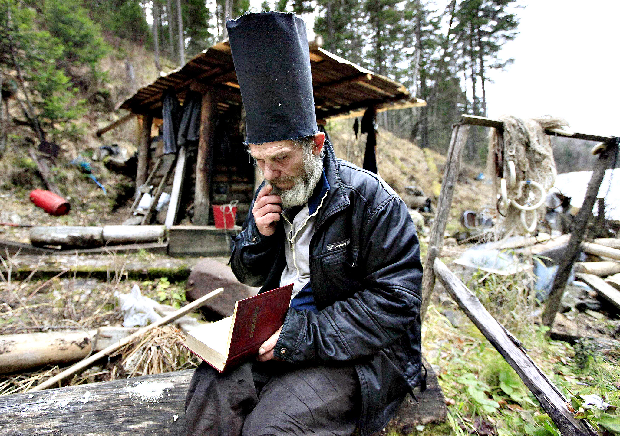 Former bargeman Viktor reads the Bible while wearing a hat he made for this purpose, outside his wooden hut located in a forest south of Russia's Siberian city of Krasnoyarsk...Former bargeman Viktor, 57, who refused to give his family name, reads the Bible while wearing a hat he made for this purpose, outside his wooden hut located in a forest some 55 km (34 miles) south of Russia's Siberian city of Krasnoyarsk, October 17, 2013. A decade ago, Viktor decided to lead the life of a hermit, and settled in this secluded forest area hidden from civilisation. He reads the Bible, and survives mainly on fish, berries, mushrooms and other food he can find.