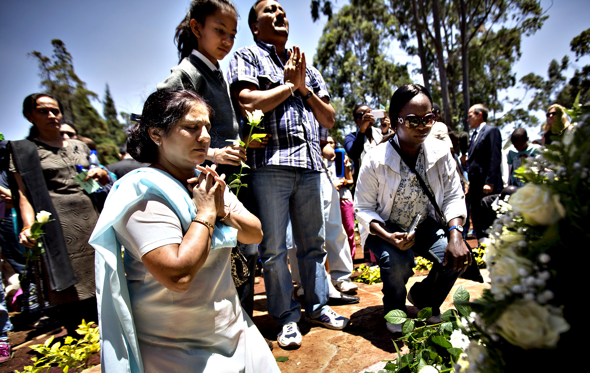 Relatives of those who died lay white roses and pray at a stone memorial, during a memorial service marking the one-month anniversary of the Sept. 21 Westgate Mall terrorist attack, in Karura Forest in Nairobi, Kenya Monday, Oct. 21, 2013. Families and friends of those killed in the attack planted trees in memory of lost loved ones in a ceremony that stressed that the attack occurred against people of all races and religions.
