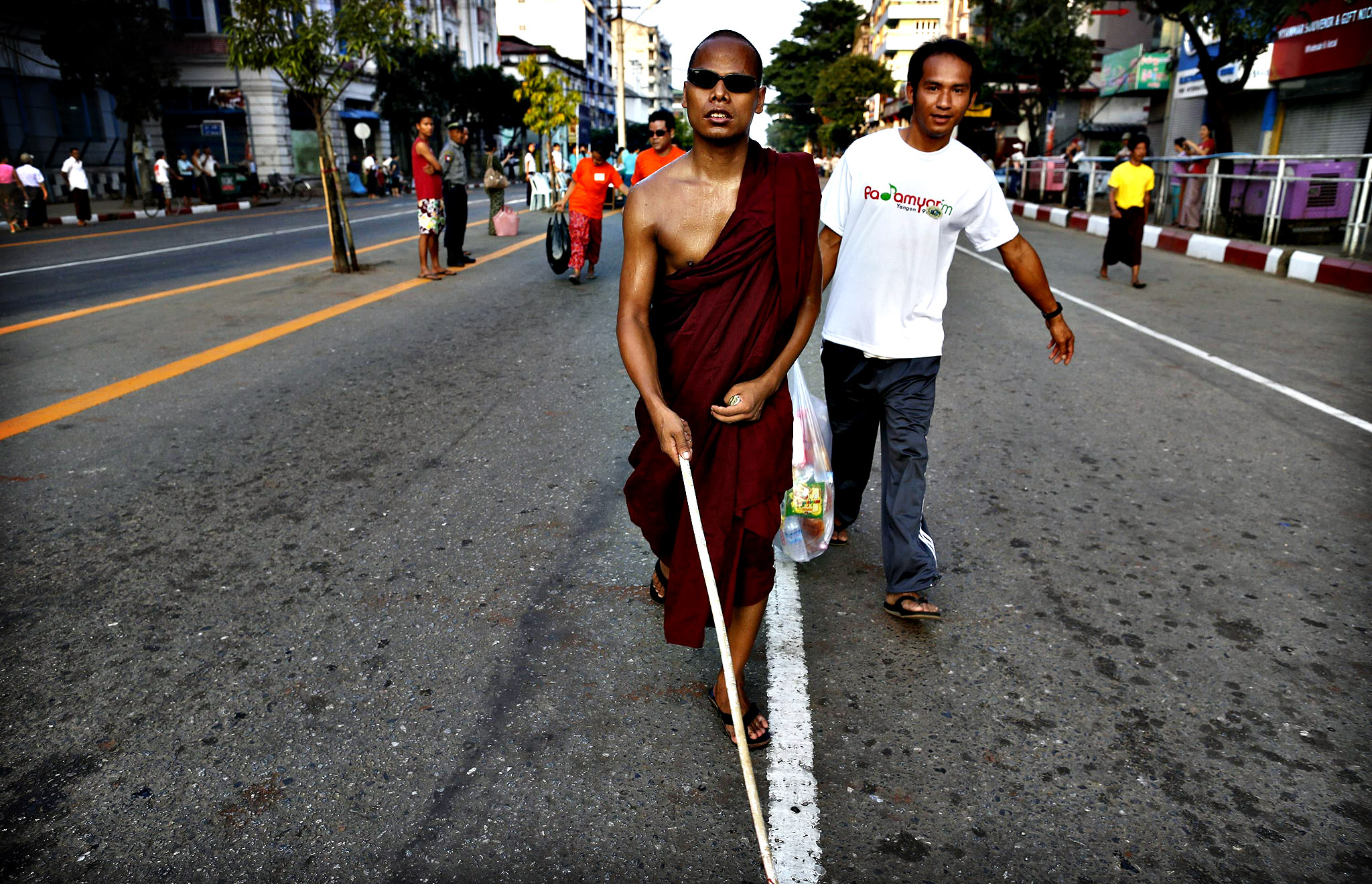 A visually impaired monk is assisted as he participates in a walk to mark White Cane Day in Yangon. About 1000 blind and visually impaired people from around Myanmar took part in the event.