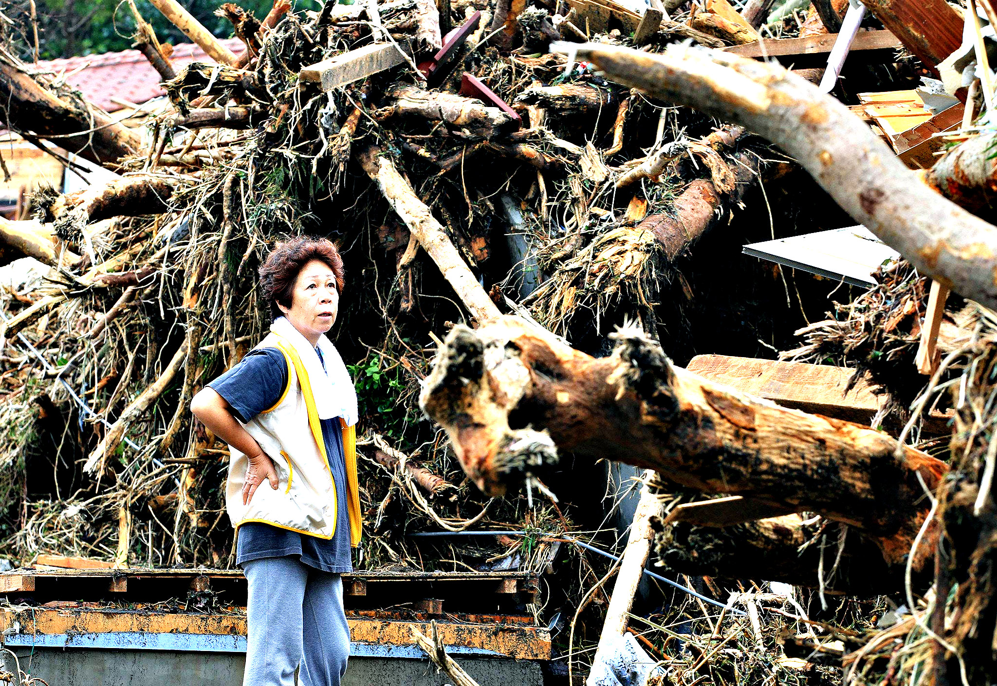 A woman reacts in front of collapsed houses following a landslide caused by Typhoon Wipha on Izu Oshima island, south of Tokyo. Eight people were killed and over 30 missing, with nearly 20,000 people ordered to evacuate and hundreds of flights cancelled as Typhoon Wipha pummelled the Tokyo region on Wednesday, leaving piles of wreckage on one small island but largely sparing the capital.  Mandatory Credit.