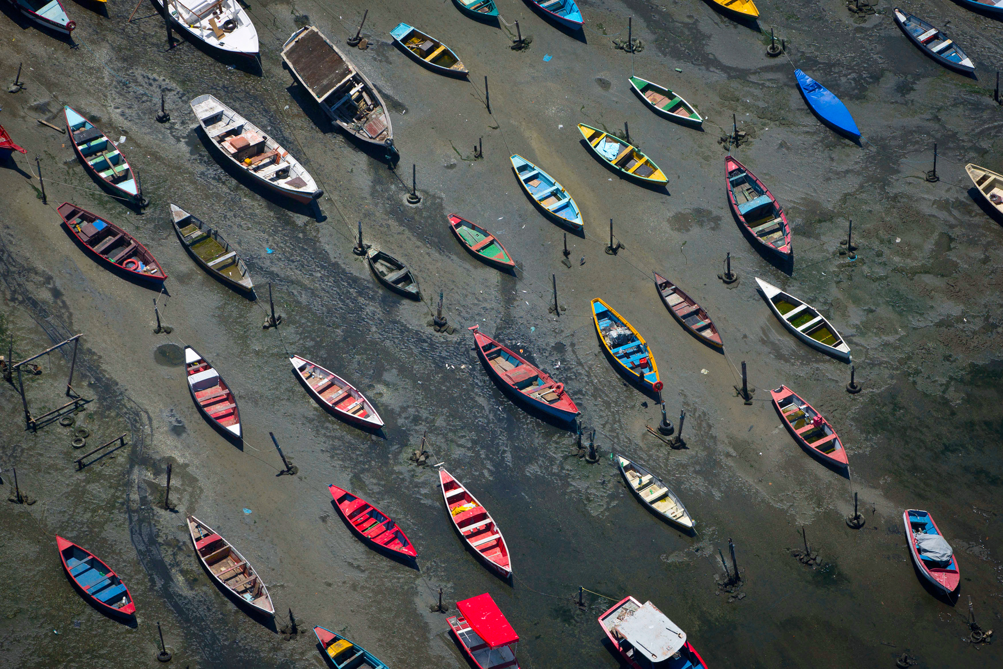 Small boats sit on the shore of Guanabara Bay in the suburb of Sao Goncalo, across the bay from Rio de Janeiro, Brazil, Tuesday, Nov. 19, 2013. The bay was home to a thriving artisanal fishing industry and popular palm-lined beaches as recently as the late-1970s, but has become a watery dump for waste from shipyards and two commercial ports. Rio de Janeiro will host the 2016 Olympic Games.