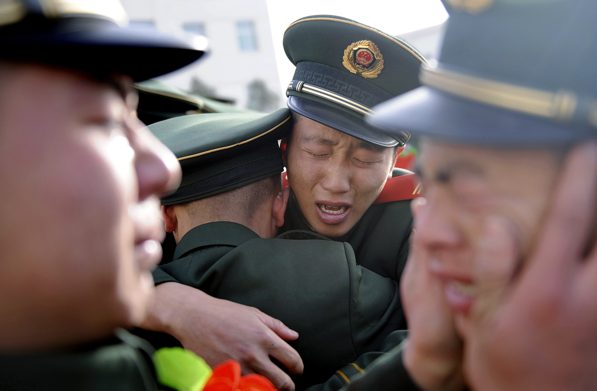 Chinese paramilitary policemen cry as they see off veterans during a farewell ceremony in Taiyuan, Shanxi province.