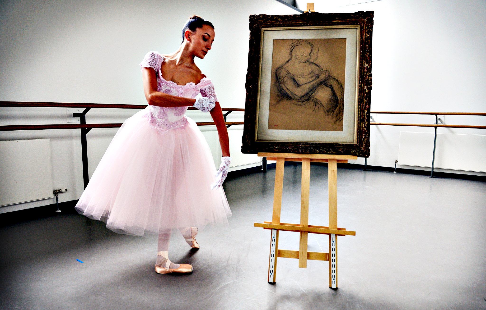 Luciana Ravizzi, a dancer at Scottish Ballet, stands next to a sketch of a ballerina by Edgar Degas, entitled 'Danseuse Rajustant L'Epaulette de Son Corsage' on November 15, 2013 in Glasgow, Scotland. The sketch is to be sold at Lyon and Turnbull fine paintings sale on the November 28, 2013. It is valued at  80,000-120,000 and is part of a collection of paintings belonging to Manchester born Albert Davis.
