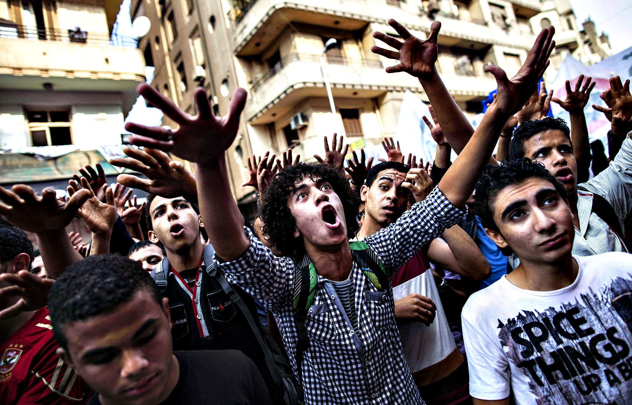 Egyptians shout slogans as they gather in Mohammed Mahmud street to mark the anniversary of anti-military protests on November 19, 2013 in Cairo. Dozens of supporters and opponents of the army gathered in Tahrir to mark the anniversary of anti-military protests, amid mounting anger over a memorial to those killed in Egypt's uprising.