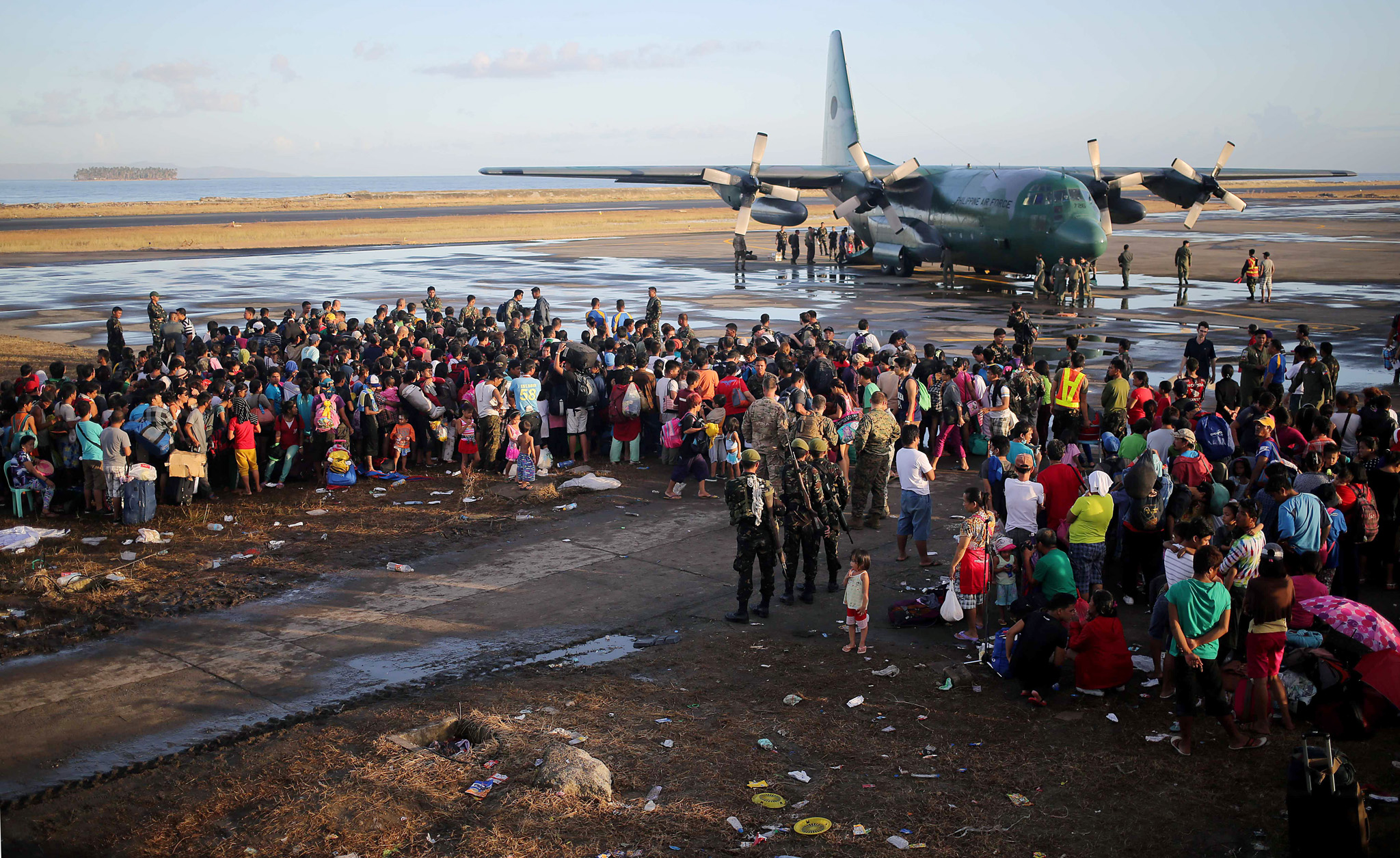 Survivors crowd around a Philippines Air force C-130 military aircraft, hoping to get on the next flight, Thursday, Nov. 14, 2013 in Tacloban city, Leyte province, central Philippines. Typhoon Haiyan, one of the strongest storms on record, slammed into 6 central Philippine islands on Friday leaving a wide swath of destruction and thousands of people dead.(AP Photo/Wong Maye-E)