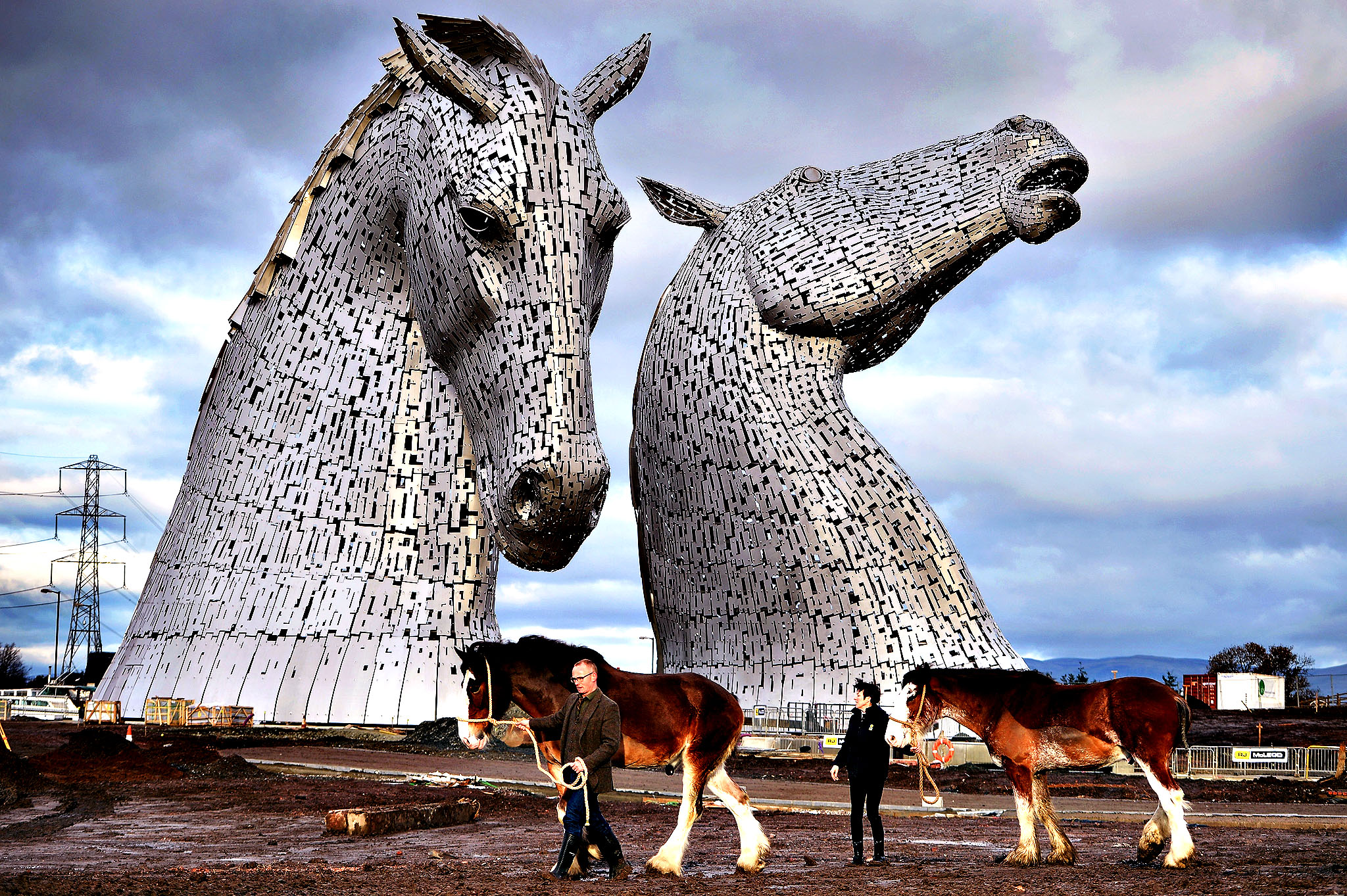 Andy Scott stands with Clydesdale Horses Duke and Baron and Donna Auchinvole during a topping out ceremony at The Kelpies on November 27, 2013 in Falkirk, Scotland. Construction work has been completed on Andy Scott's Kelpies, the world's largest pair of equine sculptures and one of the UKs tallest pieces of public art. The 30 metre tall Kelpies have cost  5million to complete and play a central role in the  43 million, 350-hectare Helix land transformational project between Falkirk and Grangemouth.