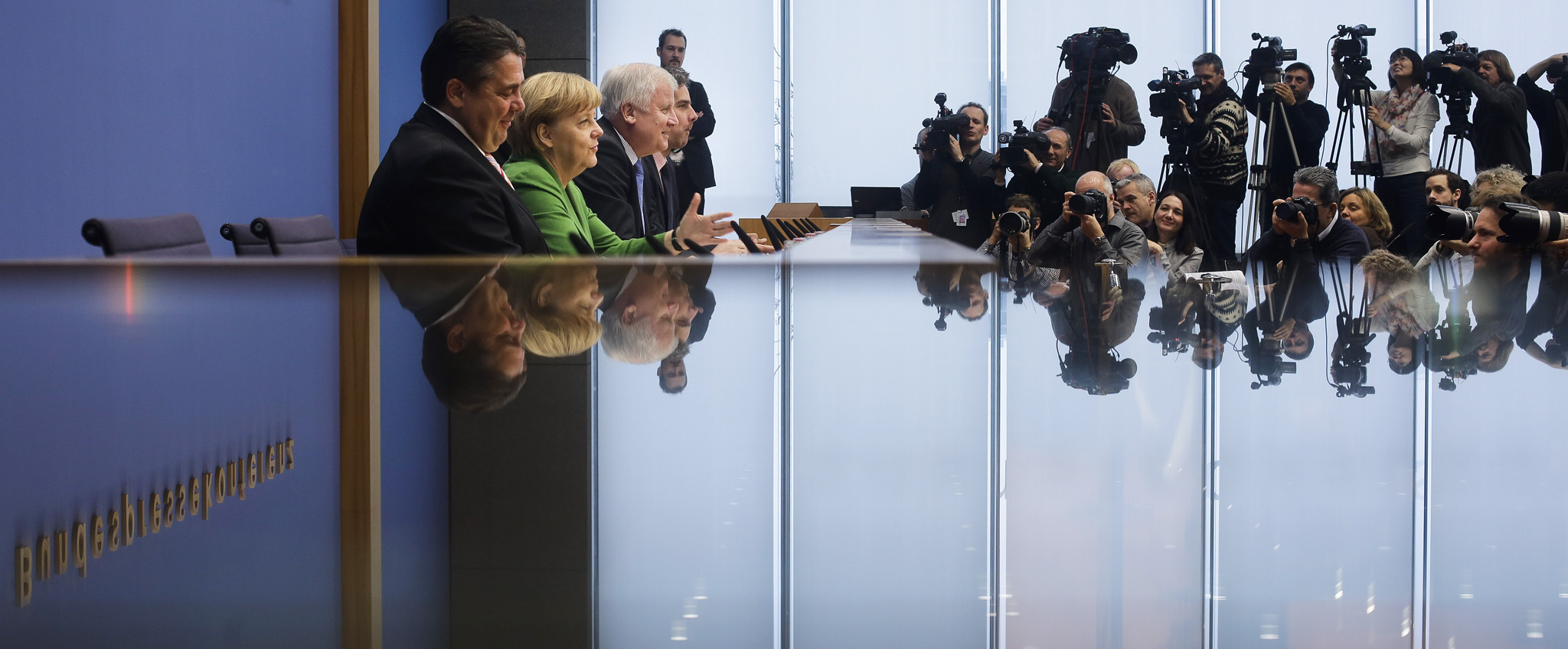 "From left, German Social Democratic Party (SPD), chairman  Sigmar Gabriel, Chancellor and chairwoman of the Christian Democratic Union (CDU), Angela Merkel and the chairman of the Christian Social Union (CSU), Horst Seehofer are reflected as they brief the media at a news conference after they signed  a coalition agreement in Berlin, Germany, Wednesday, Nov. 27, 2013. On Wednesday night Chancellor Angela Merkel's conservatives and Germany's main center-left party reached a deal to form a new government, more than two months after the country's elections. Negotiators from Merkel's Union bloc and the Social Democrats concluded their agreement to form a ""grand coalition"" of Germany's biggest parties after a final all-night round of talks.  (AP Photo/Markus Schreiber)"