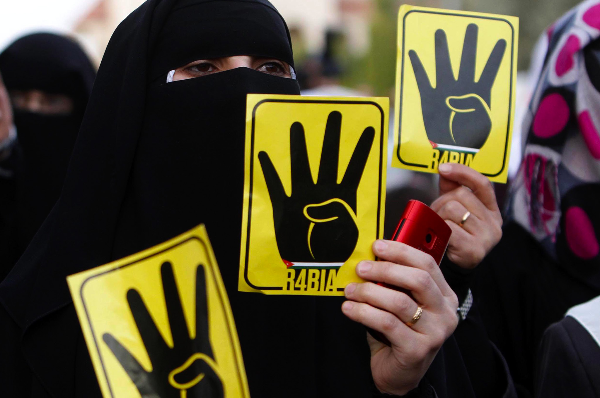 Jordanian women from Islamic Movements hold placards depicting the four-finger salute during a protest against the trial of the ousted Egyptian President Mohamed Morsi, in front of Egyptian embassy in Amman, Jordan.