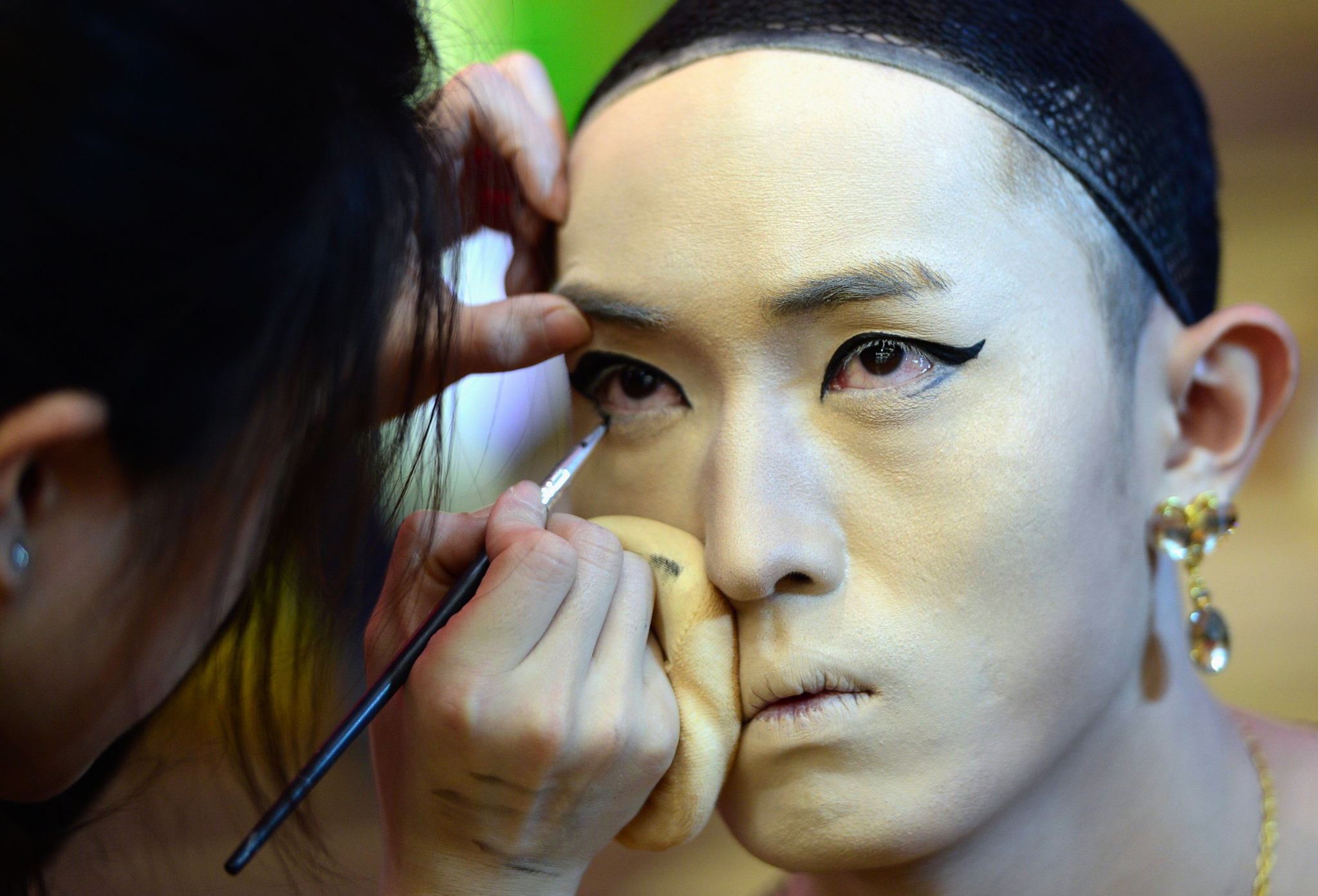 A contestant puts on makeup for a model during a stage makeup competition in Jinan, Shandong province. According to local media, each dresser contestant was assigned with one male model and the dressers' expertise were judged by to what the extent they could feminize the models' appearance.
