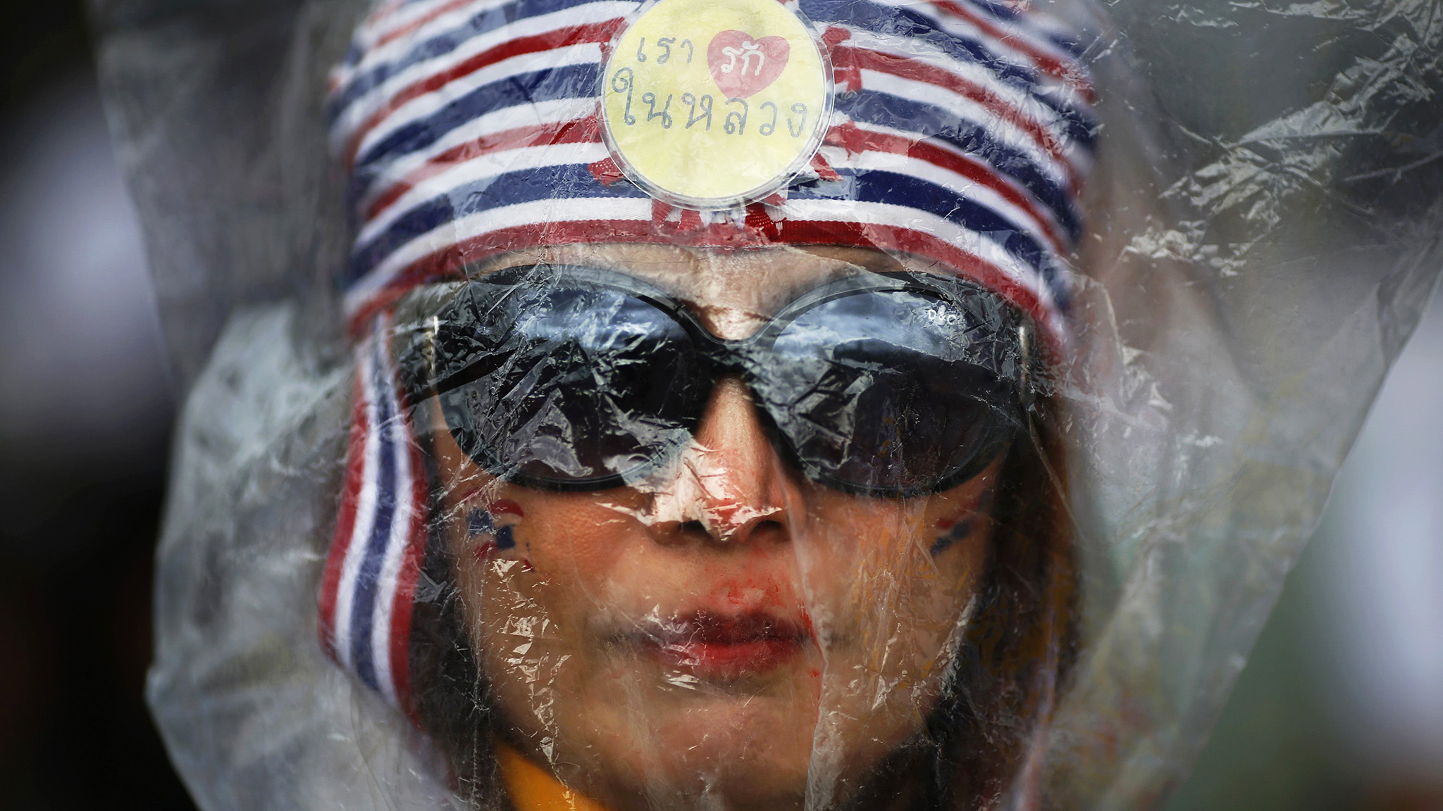 A protester against an amnesty bill wears a plastic bag over her head in front of police barricades on the main road near the government and parliament buildings in central Bangkok