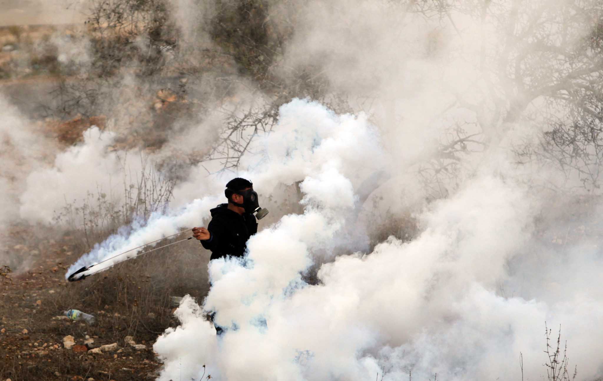 A Palestinian youth wearing a gas mask to protect against tear gas, lobs a stone during clashes with Israeli soldiers close to the Israeli Ofer military prison, near the West Bank village of Betunia