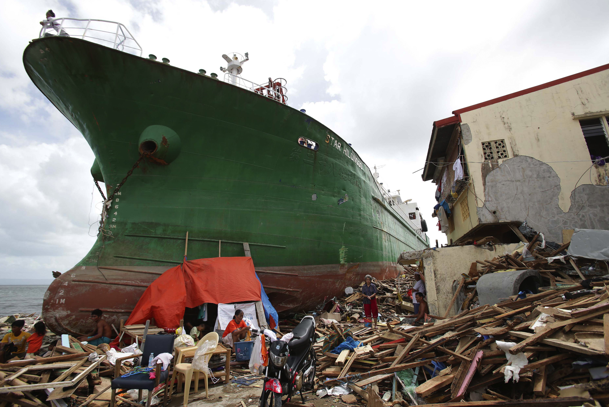 Survivors stay beside a ship that was washed ashore hitting makeshift houses near an oil depot in Tacloban city, Leyte province central Philippines.