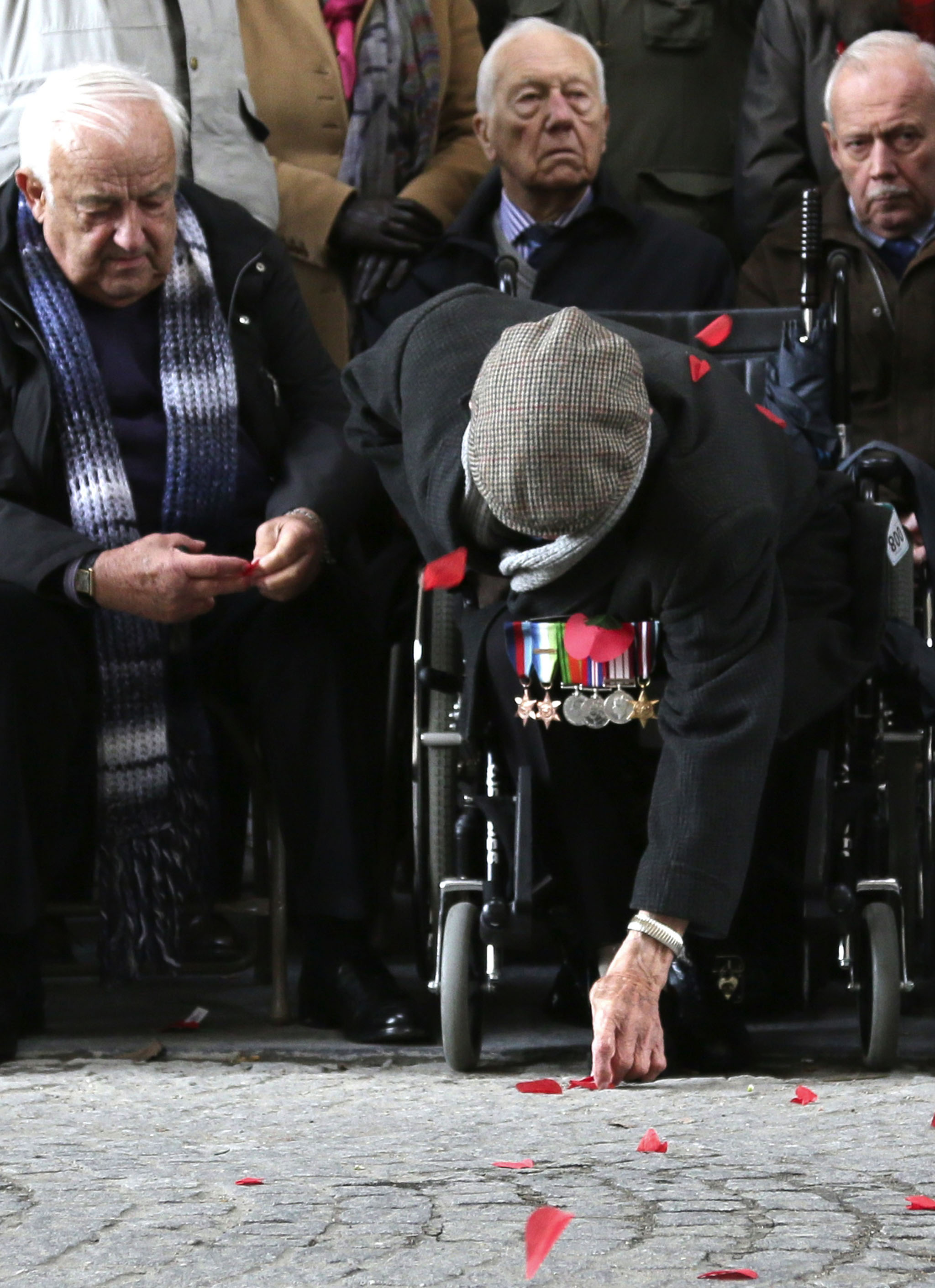 World War Two veteran Harry Marrington, from Portsmouth, England, leans down to pick up a paper poppy during an Armistice Day ceremony under the Menin Gate in Ypres, Belgium. The Menin Gate Memorial bears the names of more than 54,000 British and Commonwealth soldiers who were killed in the Ypres Salient of World War I and whose graves are not known.