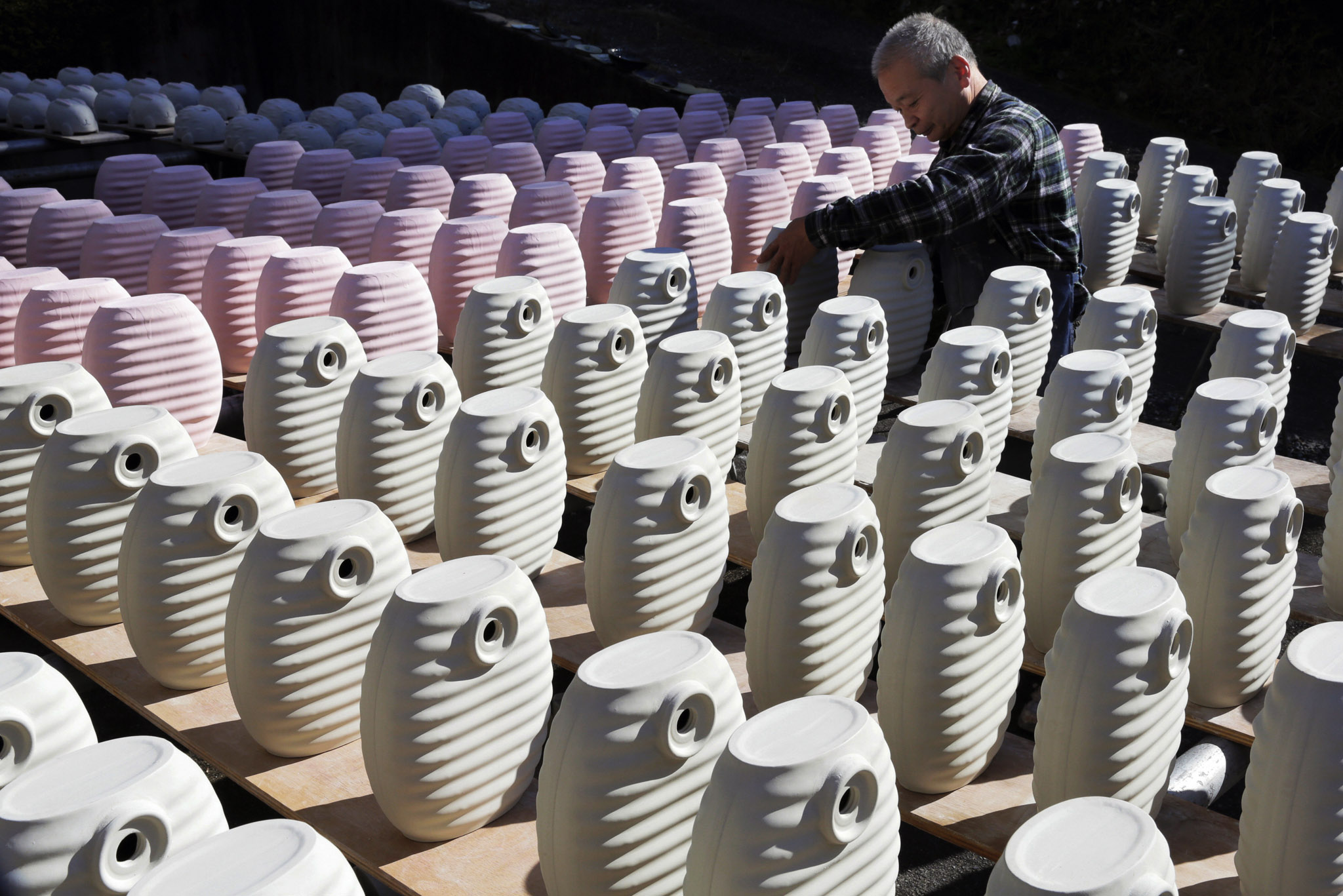 A worker dries ceramic hot water bottles in the sun before they are fired in a kiln in Tajimi, Gifu, Japan. The traditional ceramic bottle became popular again about 10 years ago as people rediscovered they were a great way to keep warm and required minimum use of electricity. They are popular among office workers, who use the ceramic bottles to keep their feet warm