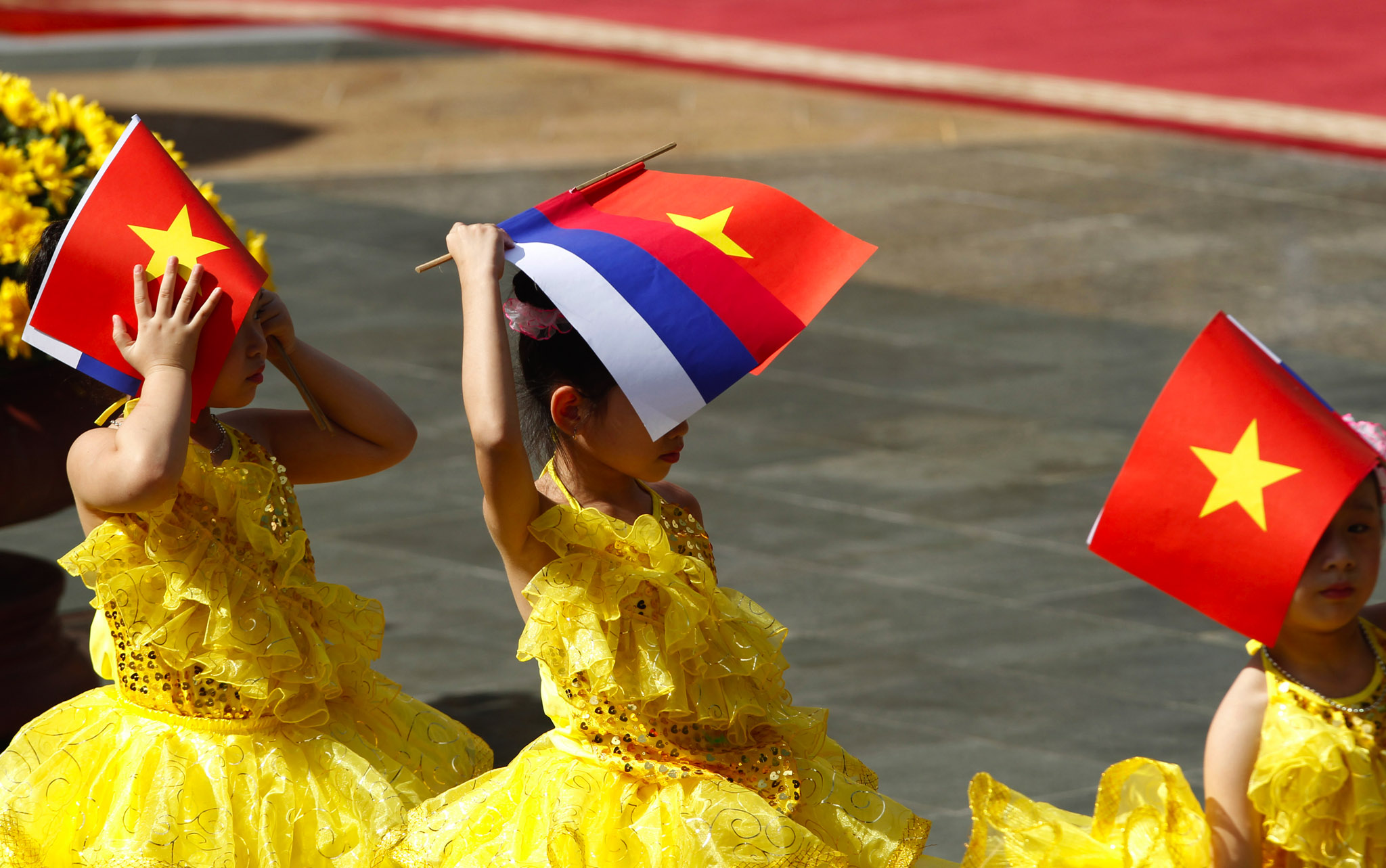 Vietnamese children cover their faces with Vietnamese and Russian flags while waiting for the arrival of Russian President Vladimir Putin for a welcoming ceremony at the Presidential Palace in Hanoi.