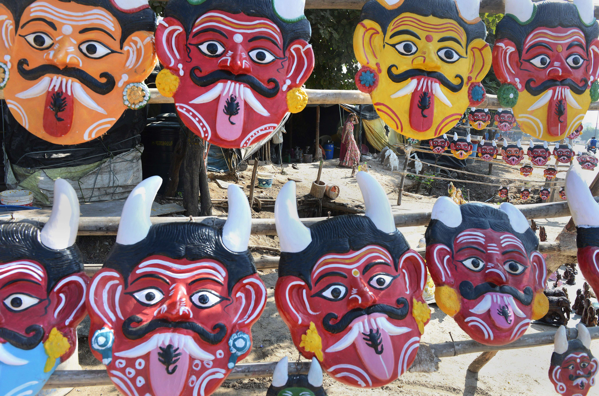 An Indian labourer walks through a stall selling masks depicting the devil, and believed to ward off evil if hung outside homes, outside a makeshift shelter on a highway on the outskirts of Hyderabad.