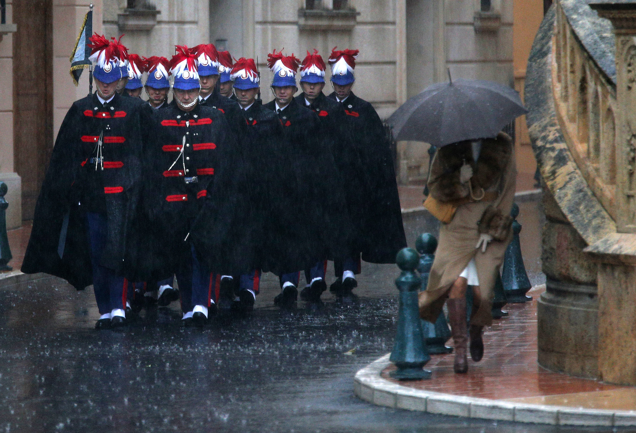 Guardsman arrive in the rain at the cathedral in Monaco before the mass for the Monaco's National Day.