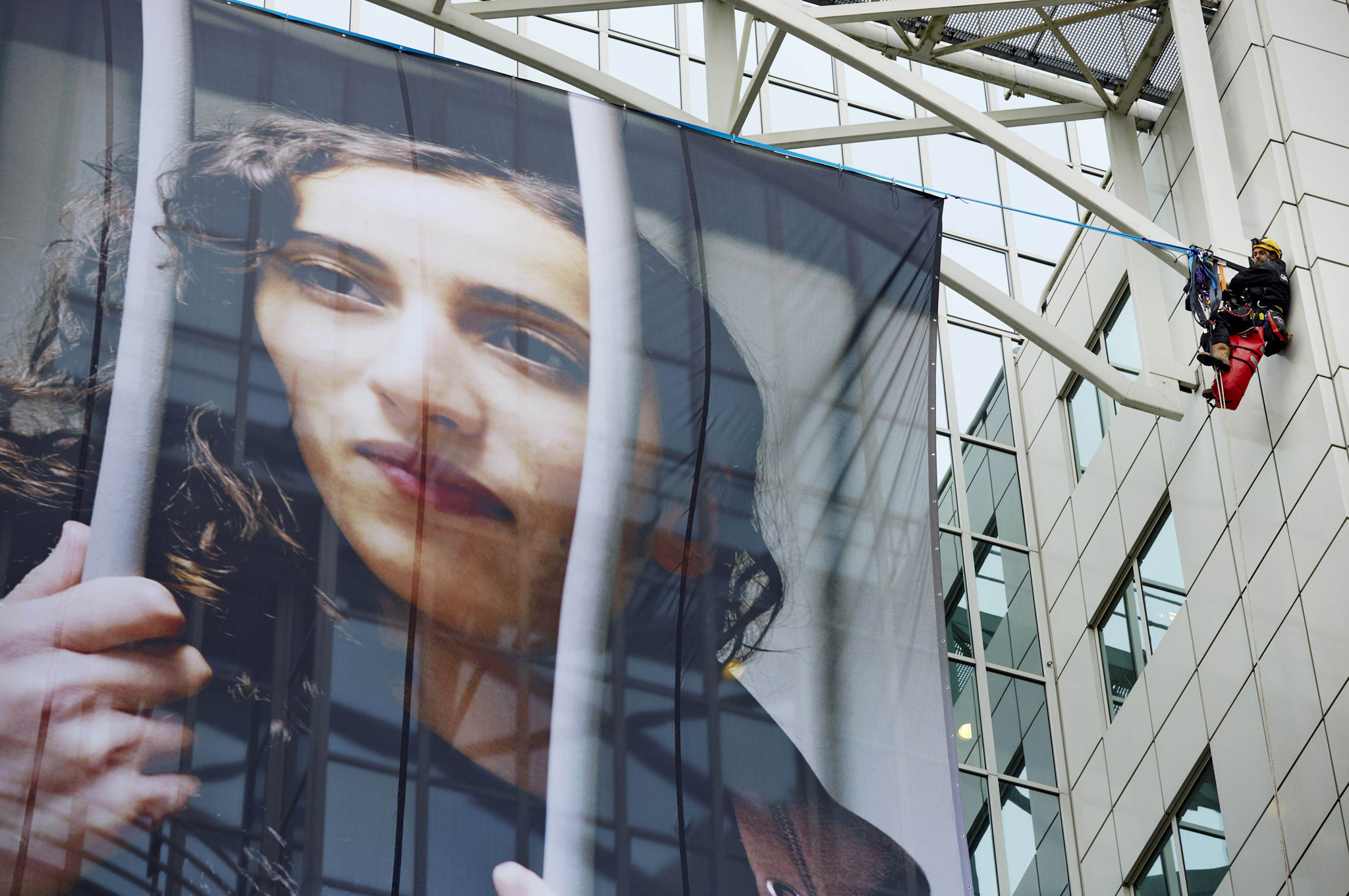 "Members of Greenpeace hang a large poster of Dutch activist Faiza Oulahsen on the office building of Shell during a protest calling for the release of the ""Arctic 30"" in Rotterdam."