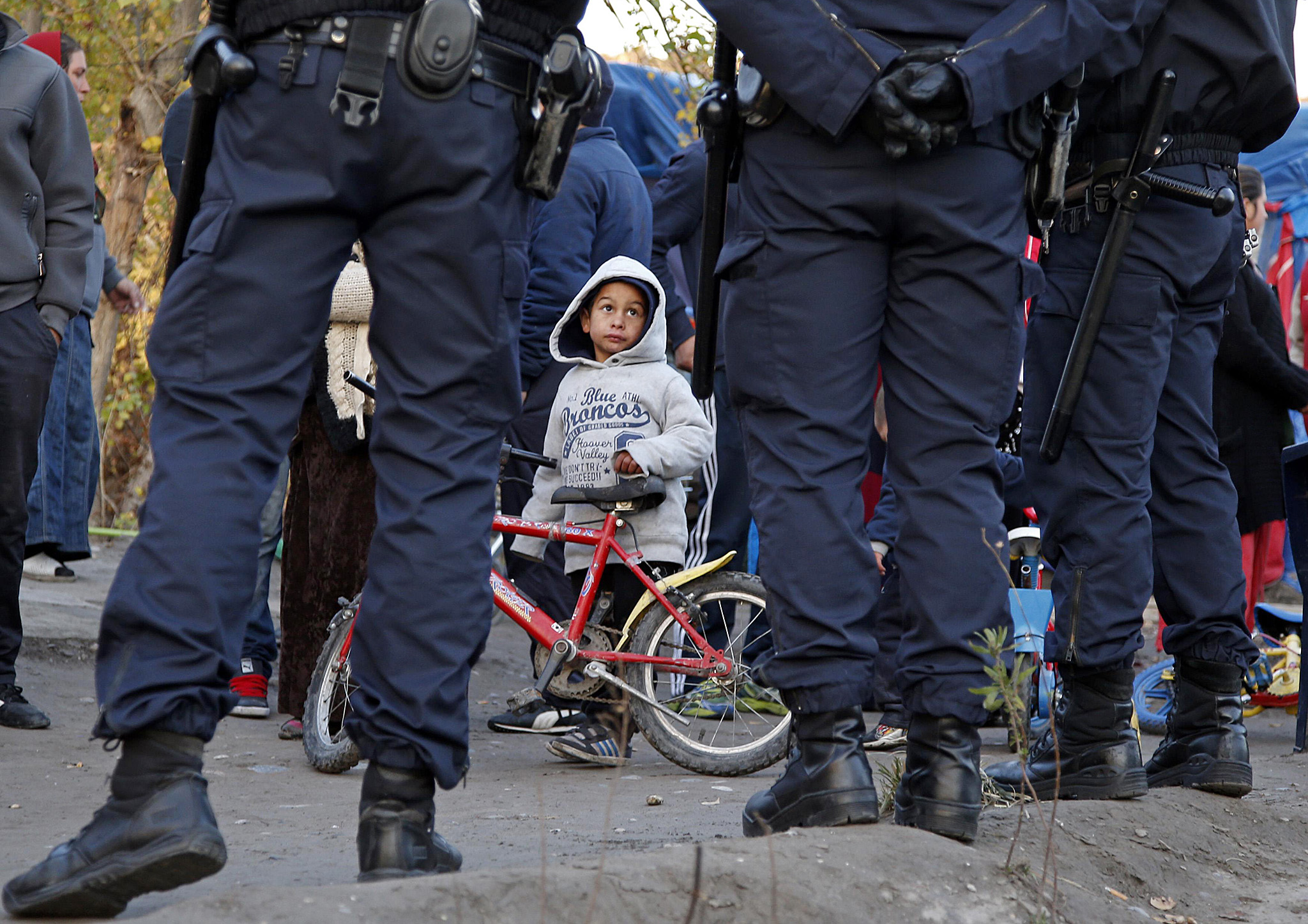 A Roma child looks at French police standing guard as Roma families are evacuated from their illegal camp near the Var river in Nice...A Roma child looks at French police standing guard as Roma families are evacuated from their illegal camp near the Var river in Nice, southeastern France, November 27, 2013.  REUTERS/Eric Gaillard