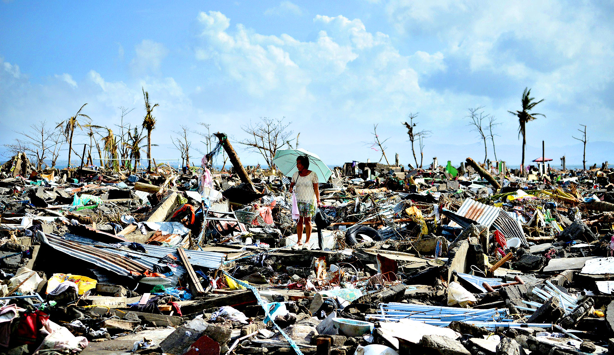 A surivor walks among the debris of houses destroyed by Super Typhoon Haiyan in Tacloban in the eastern Philippine island of Leyte on November 11, 2013. The United States, Australia and the United Nations mobilised emergency aid to the Philippines as the scale of the devastation unleashed by Super Typhoon Haiyan emerged on November 11.