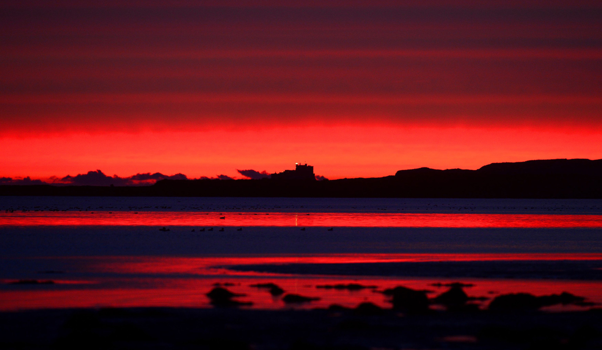 Autumn weather Nov 26th...A glowing sunrise this morning over Bamburgh Castle in Northumberland. PRESS ASSOCIATION Photo. Picture date: Tuesday November 26, 2013.