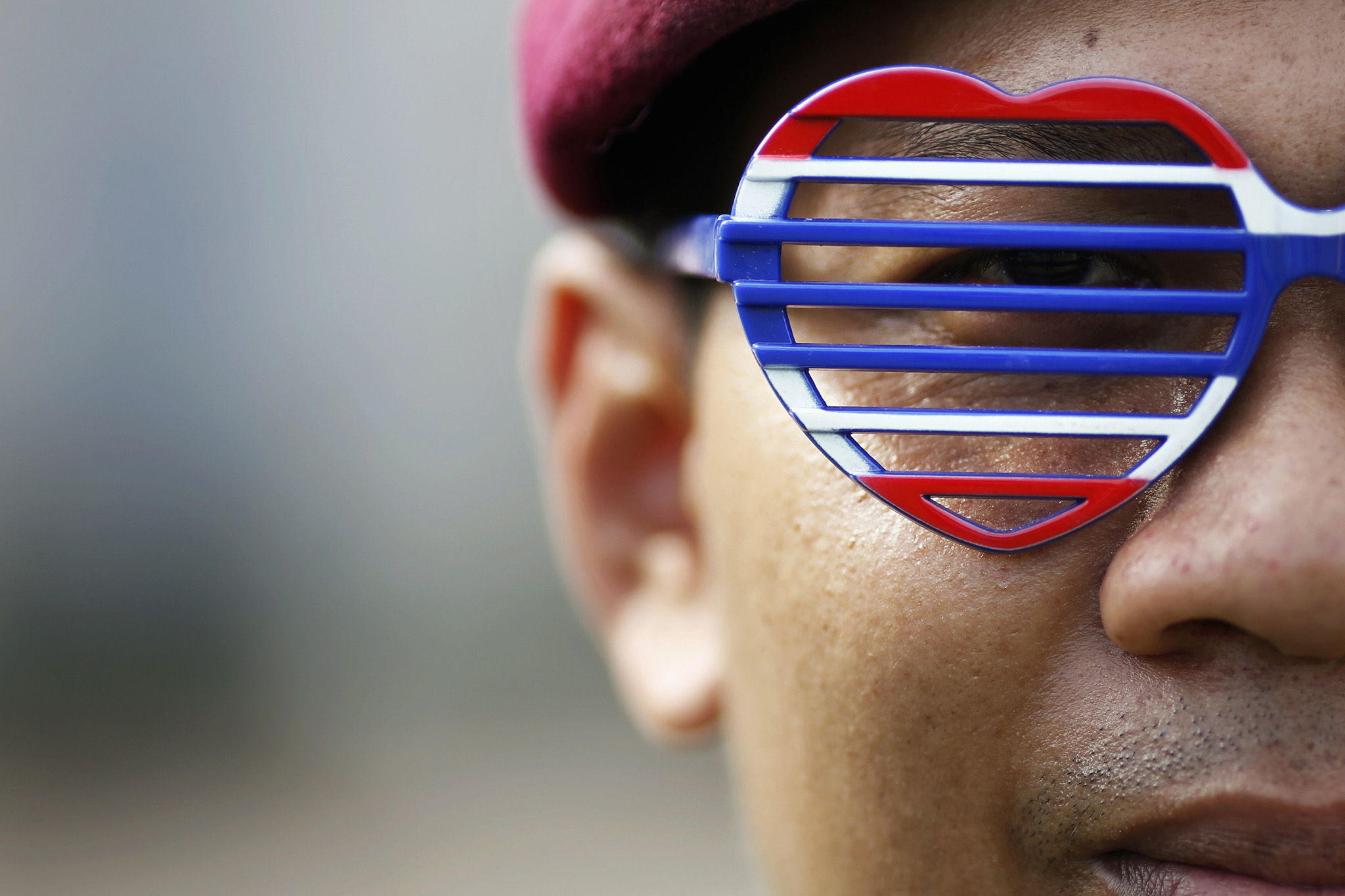 A soldier wears glasses given to him by an anti-government protester who broke in  with others into the compound of the Royal Thai Army headquarters in Bangkok...A soldier wears glasses given to him by an anti-government protester who broke in with others into the compound of the Royal Thai Army headquarters in Bangkok November 29, 2013. About 1,500 anti-government protesters forced their way into the compound of Thailand's army headquarters on Friday, the latest escalation in a city-wide demonstration seeking to topple Prime Minister Yingluck Shinawatra.  REUTERS/Damir Sagolj